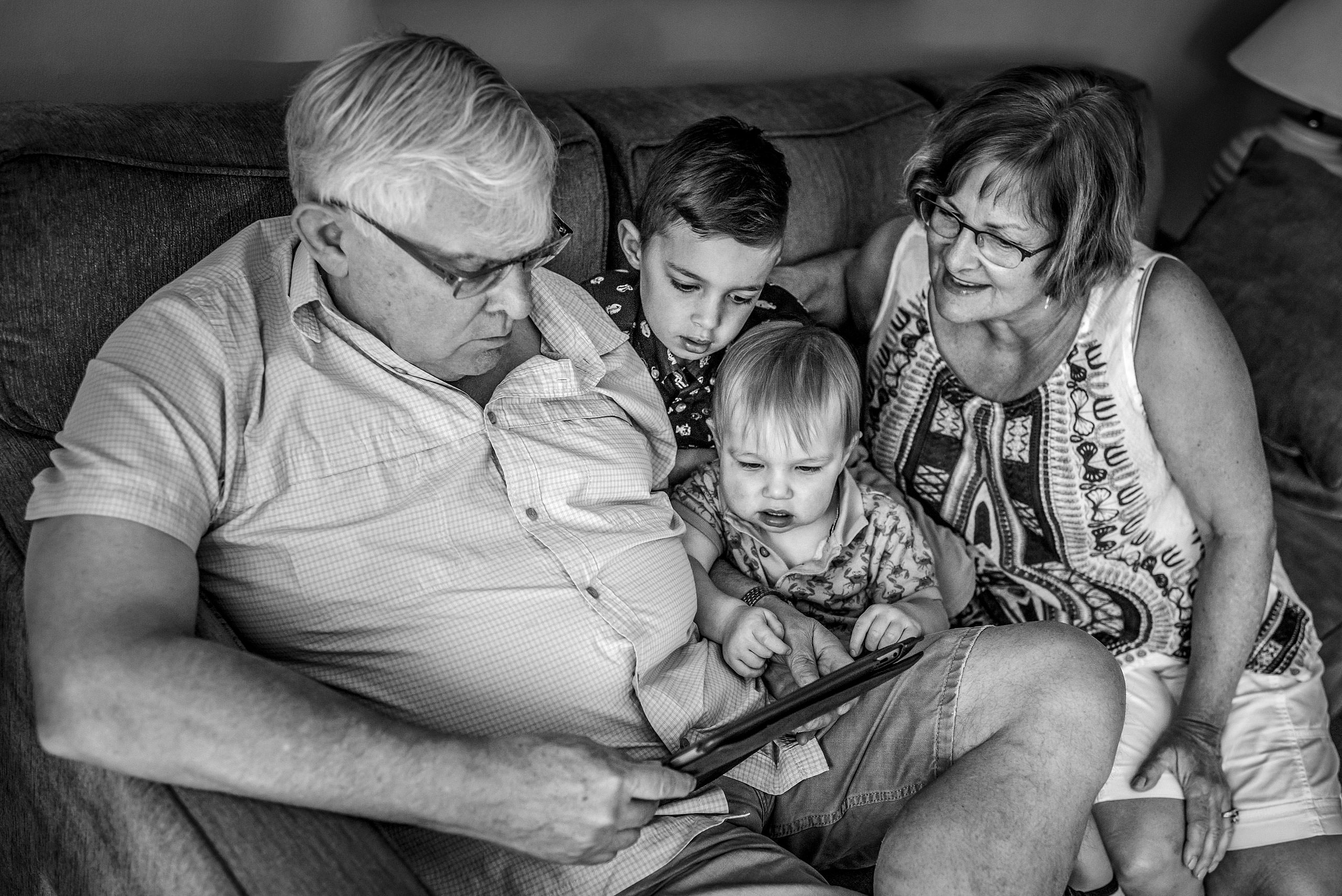 grandma and grandpa with their grandsons looking at an iPad by destination family photographers sean leblanc