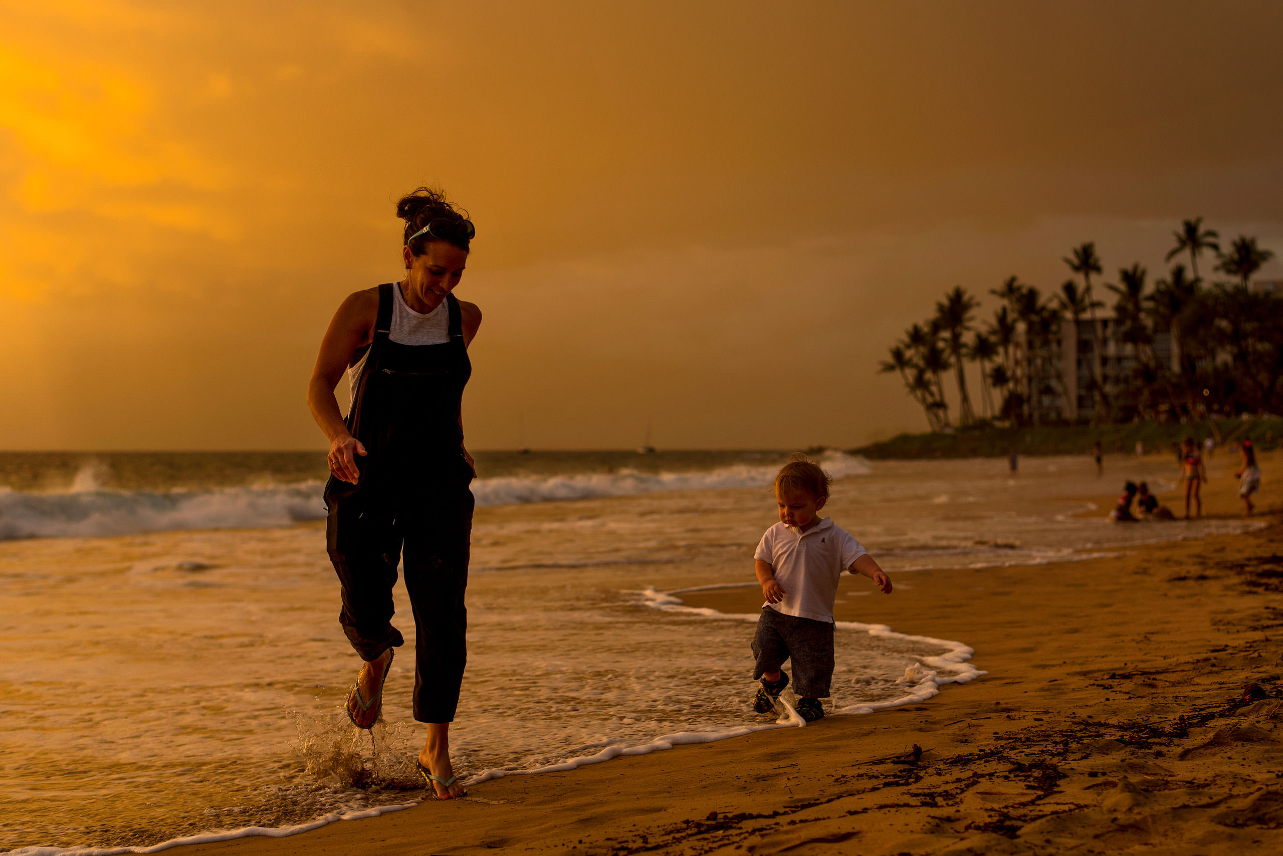 a mom and her son running on the beach by destination family photographers sean leblanc