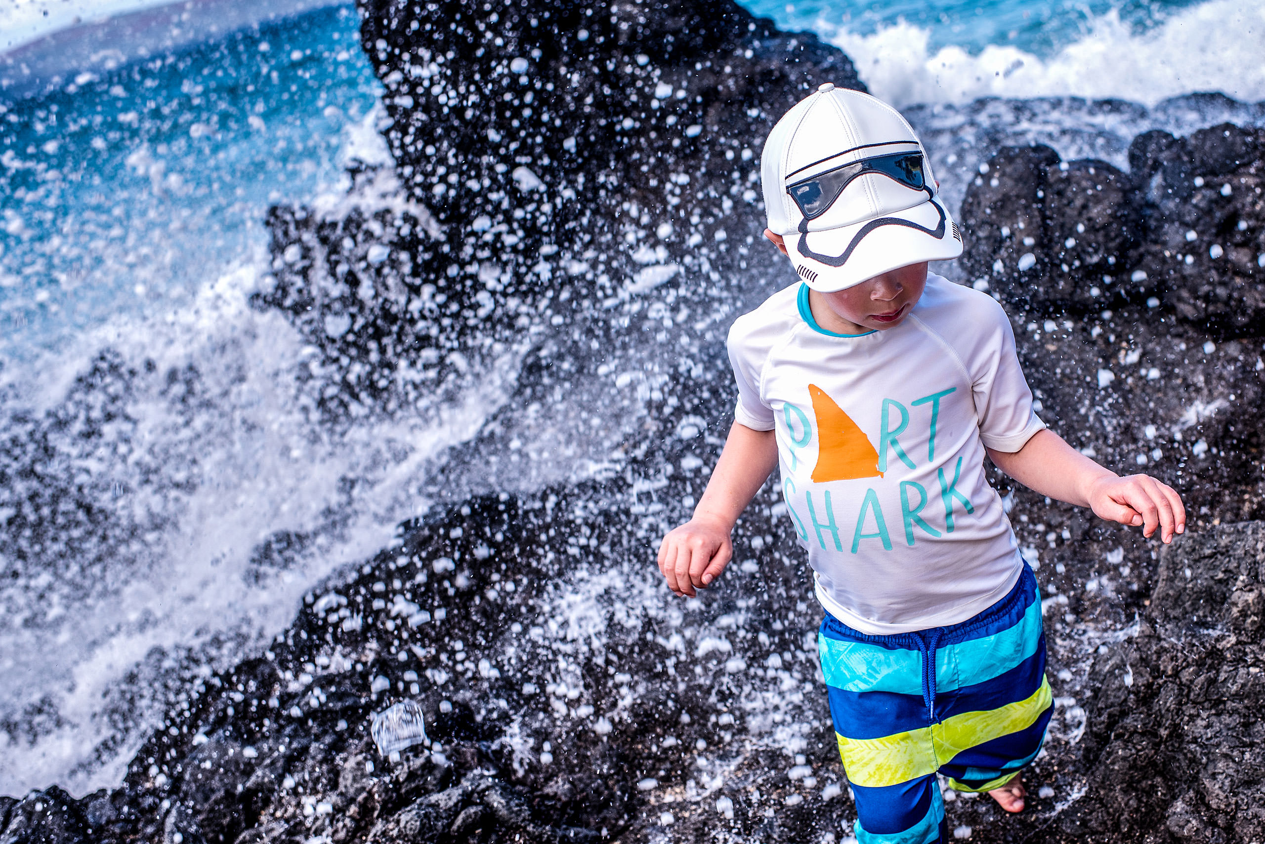 a young boy being splashed by water by destination family photographers sean leblanc
