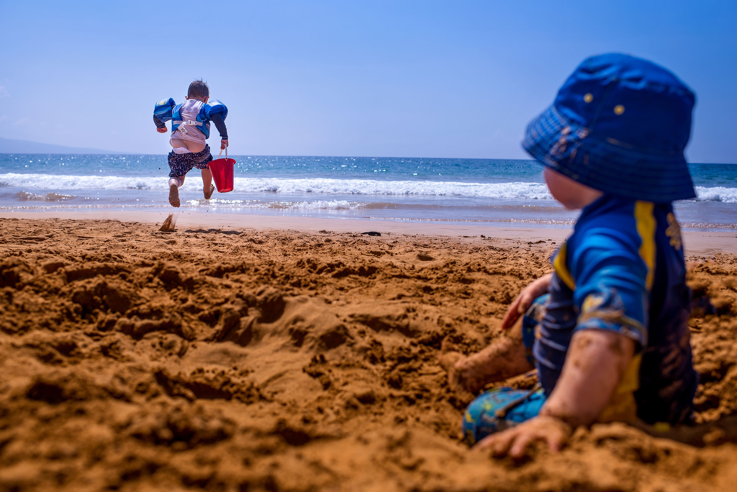 a boy running on a beach towards the ocean by destination family photographers sean leblanc