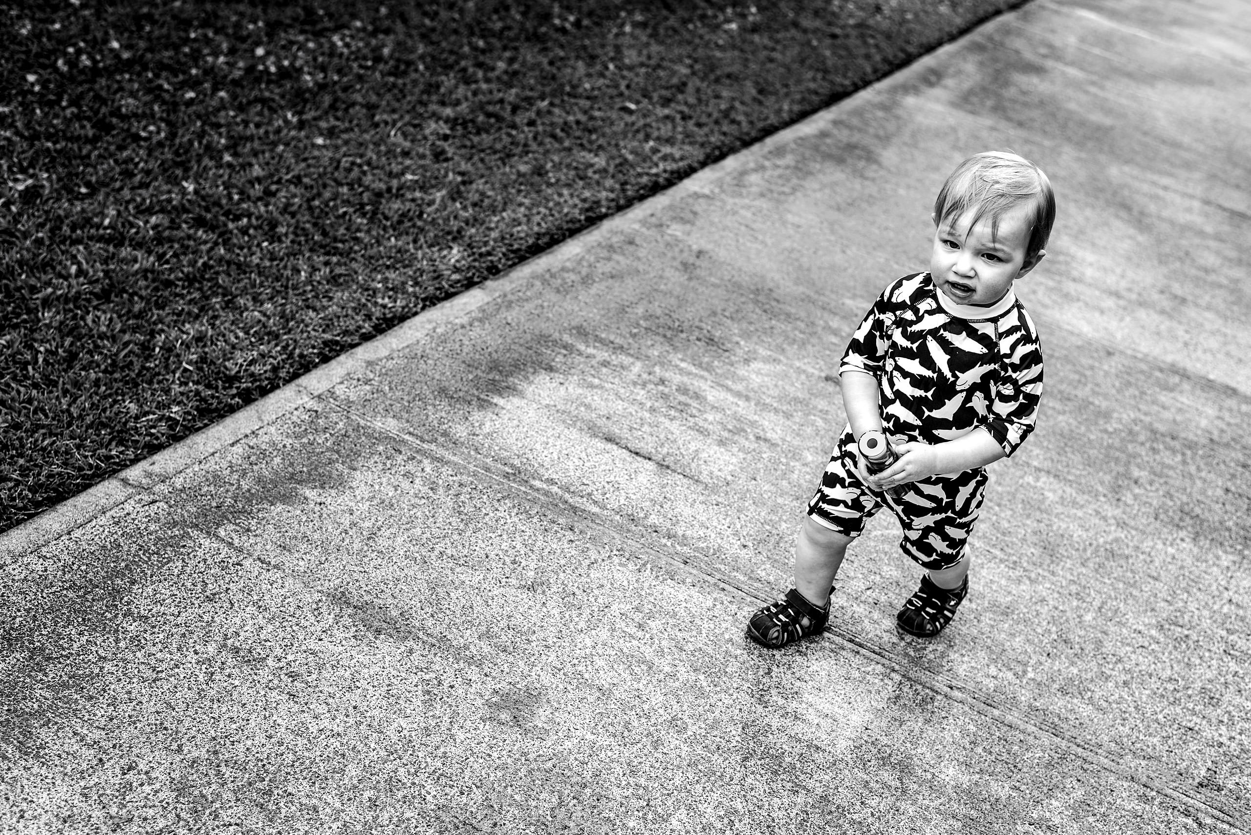 a young boy walking in his bathing suit on the sidewalk by destination family photographers sean leblanc