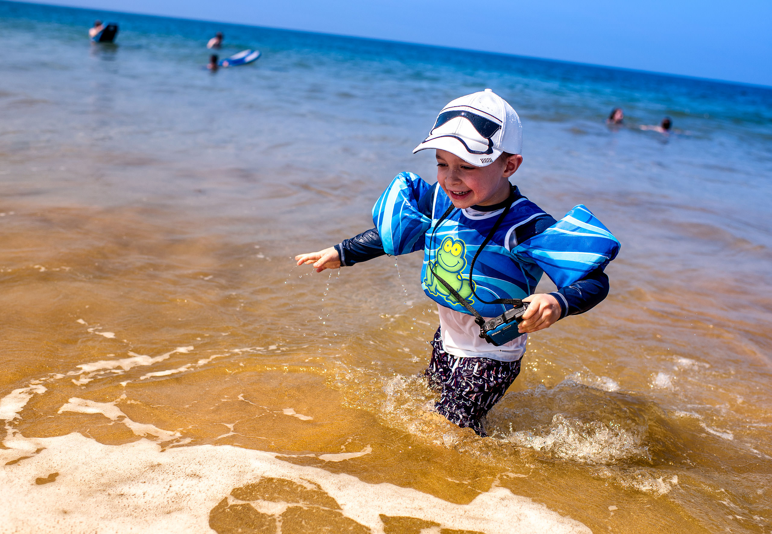 a young boy playing in the ocean by destination family photographers sean leblanc