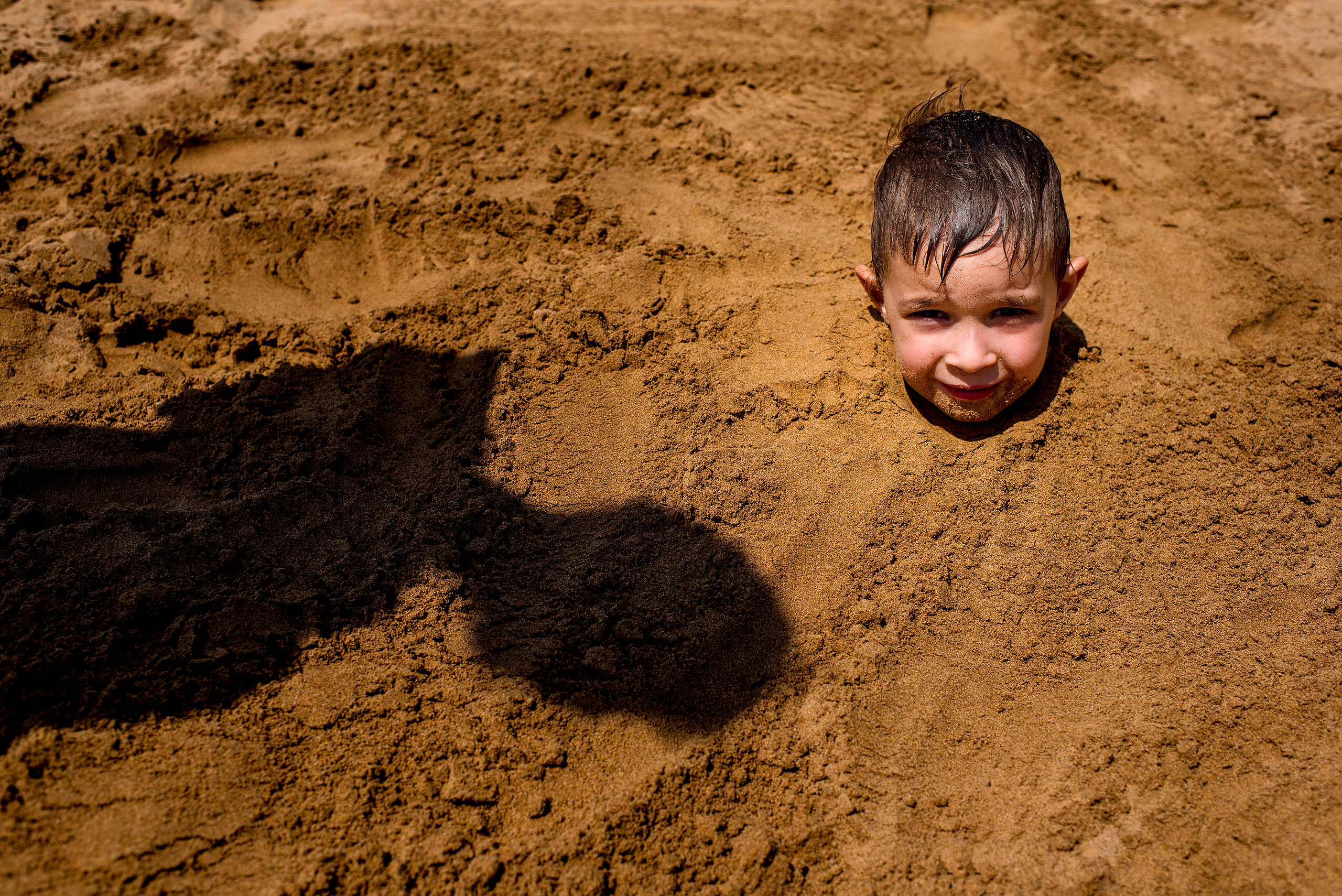 a young boy buried in the sand up to his neck by destination family photographers sean leblanc