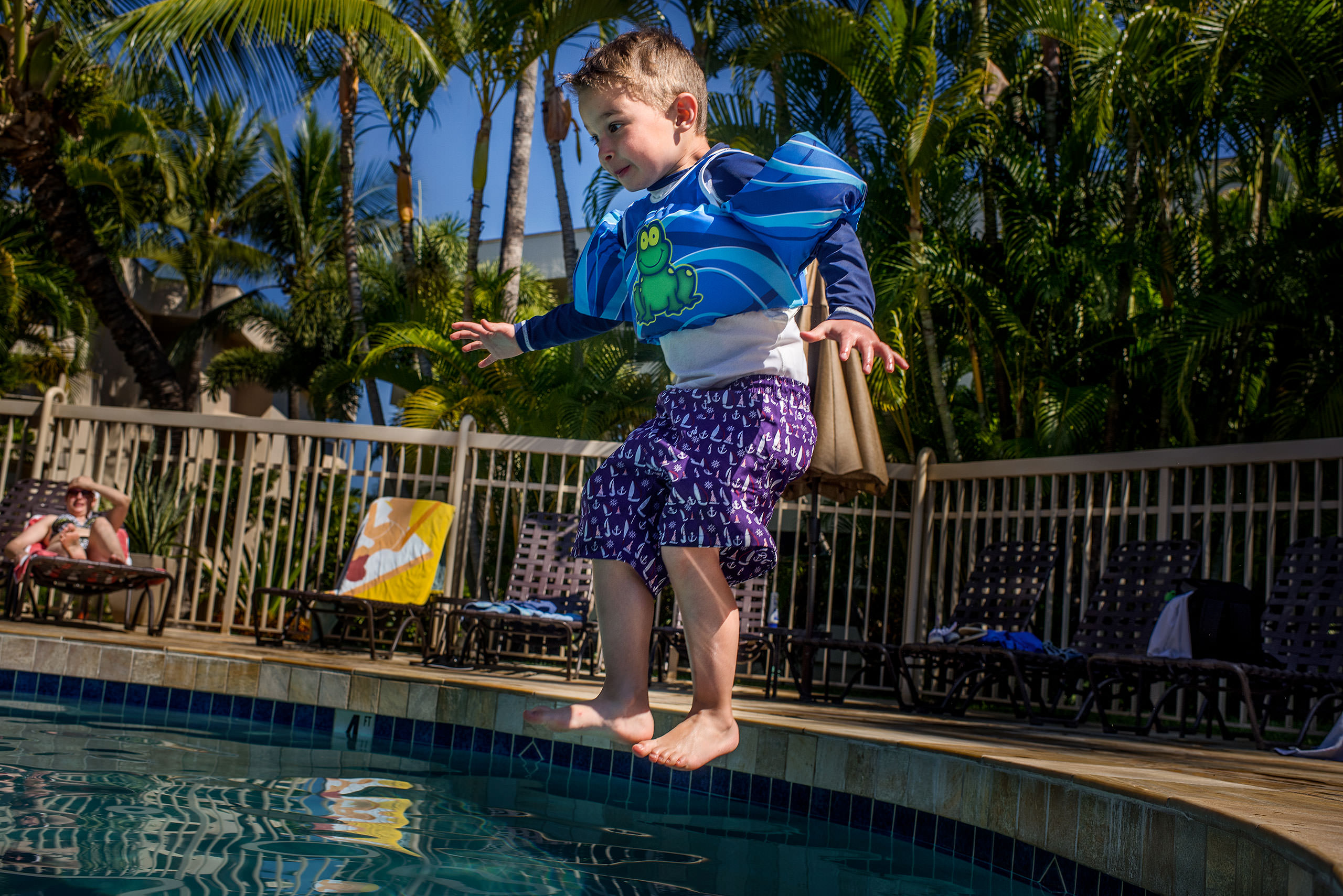 a young boy jumping into a pool by destination family photographers sean leblanc