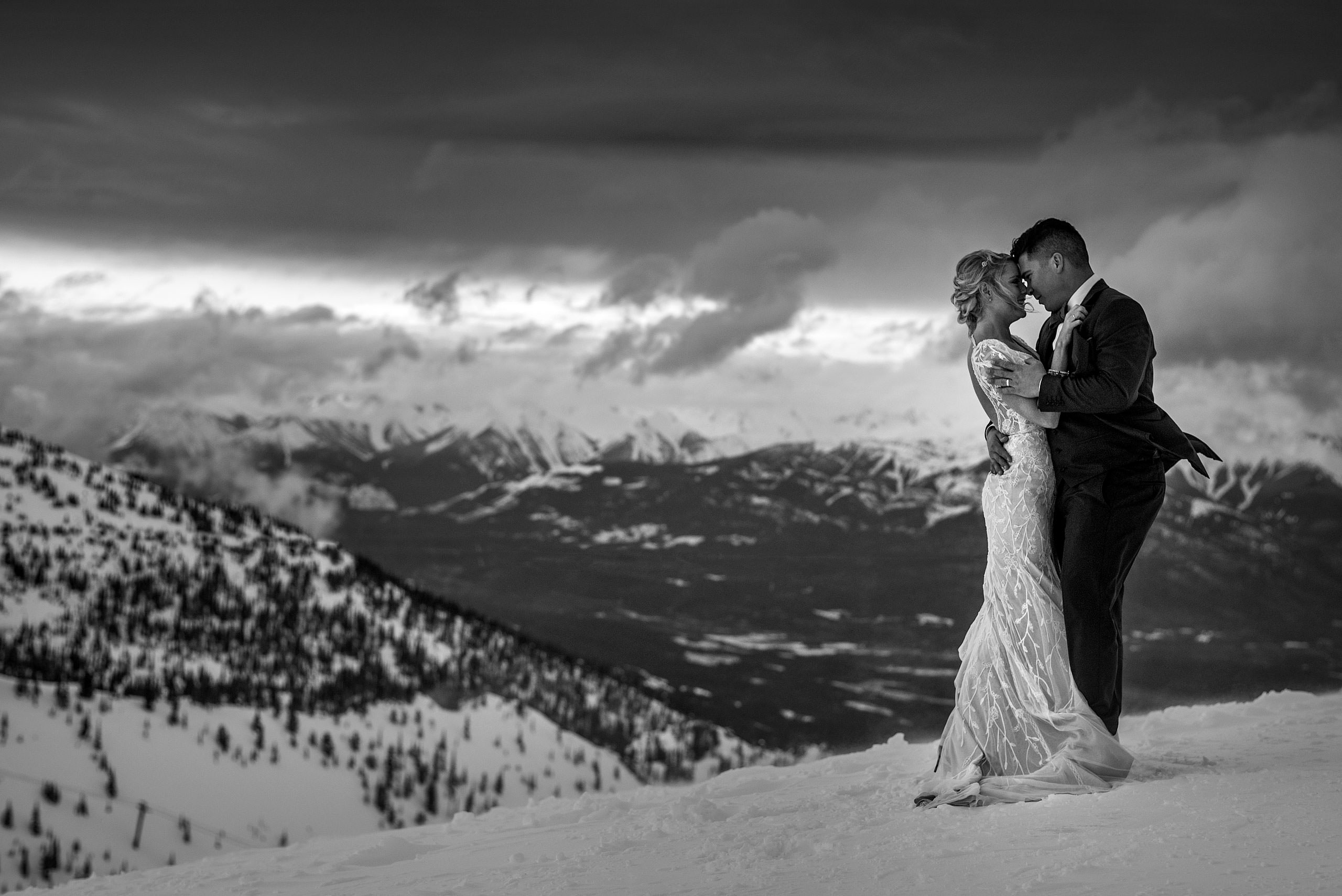bride and groom embracing at the top of a mountain at winter kicking horse wedding