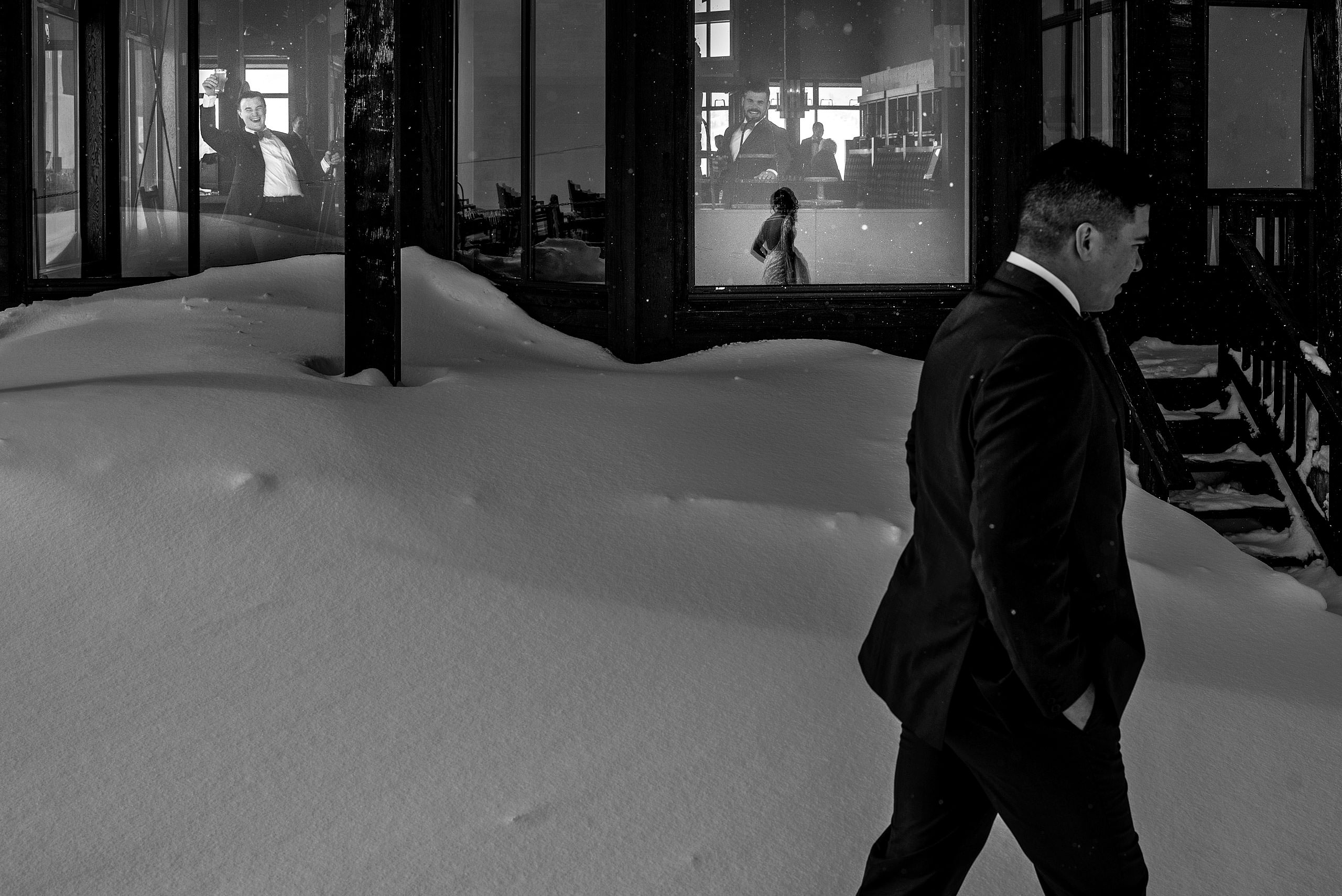 groom walking past a building at winter kicking horse wedding
