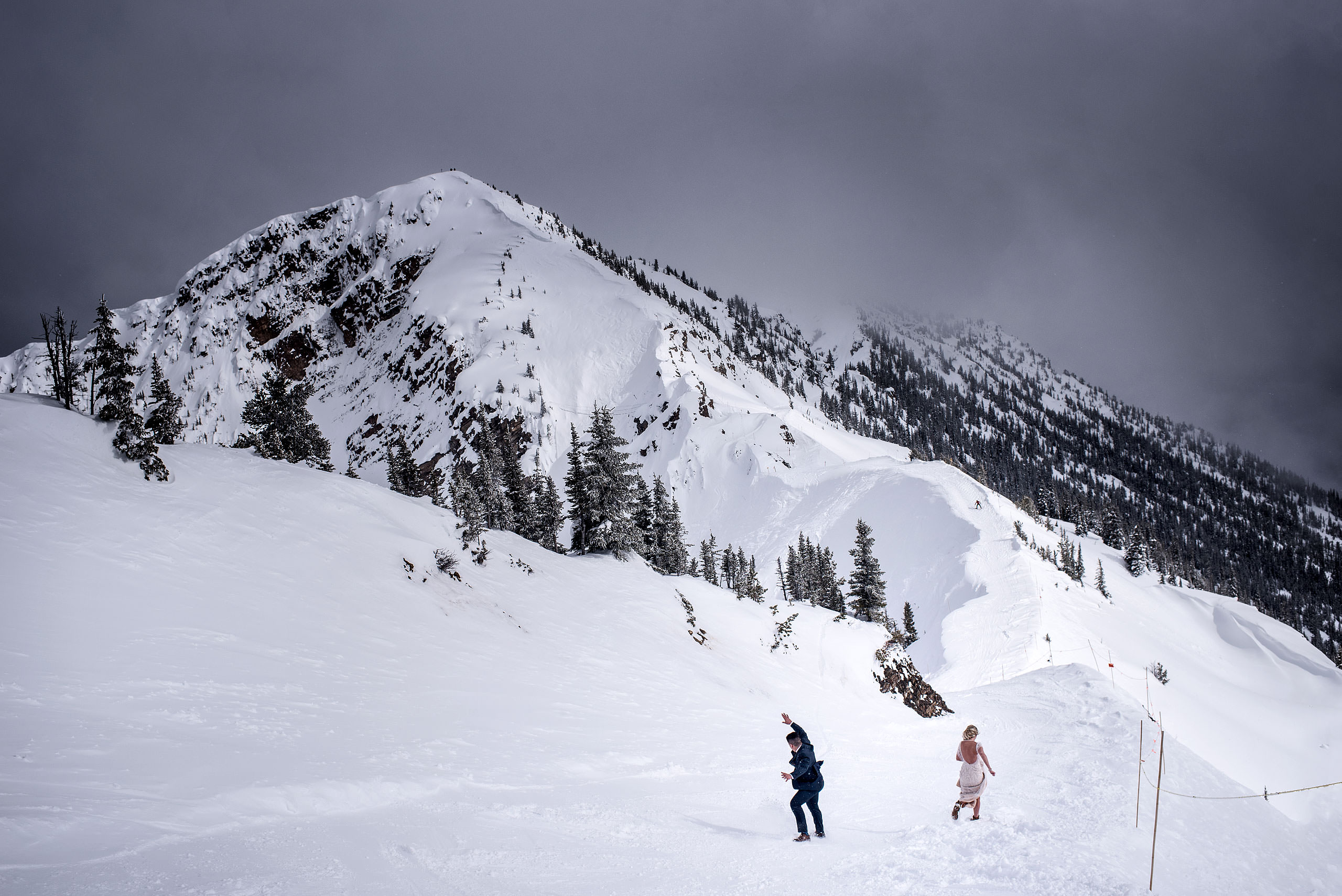 a bride and groom sliding down the side of a mountain at a winter kicking horse wedding by sean leblanc