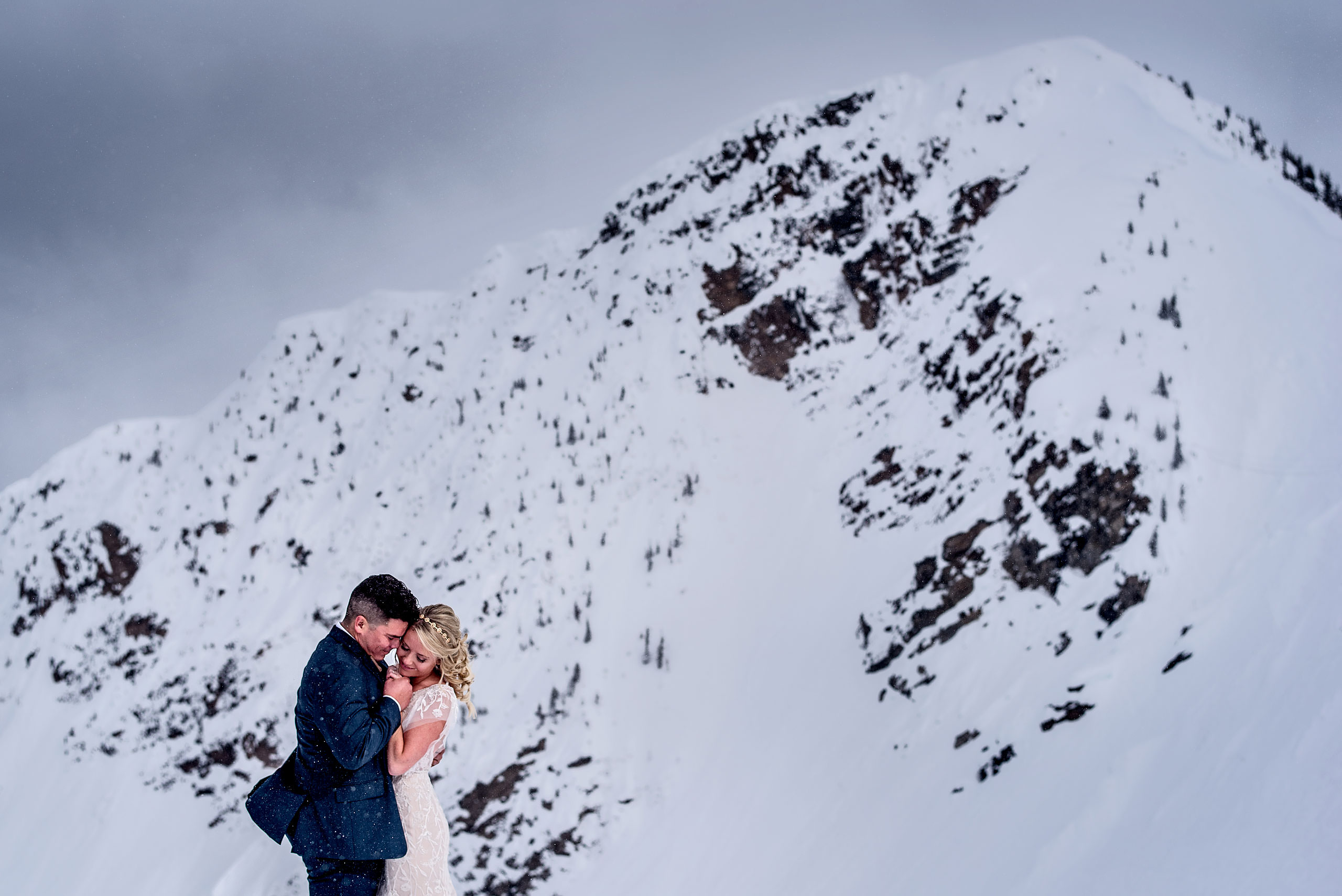 a bride and groom embracing each other in front of a mountain at a winter kicking horse wedding by sean leblanc