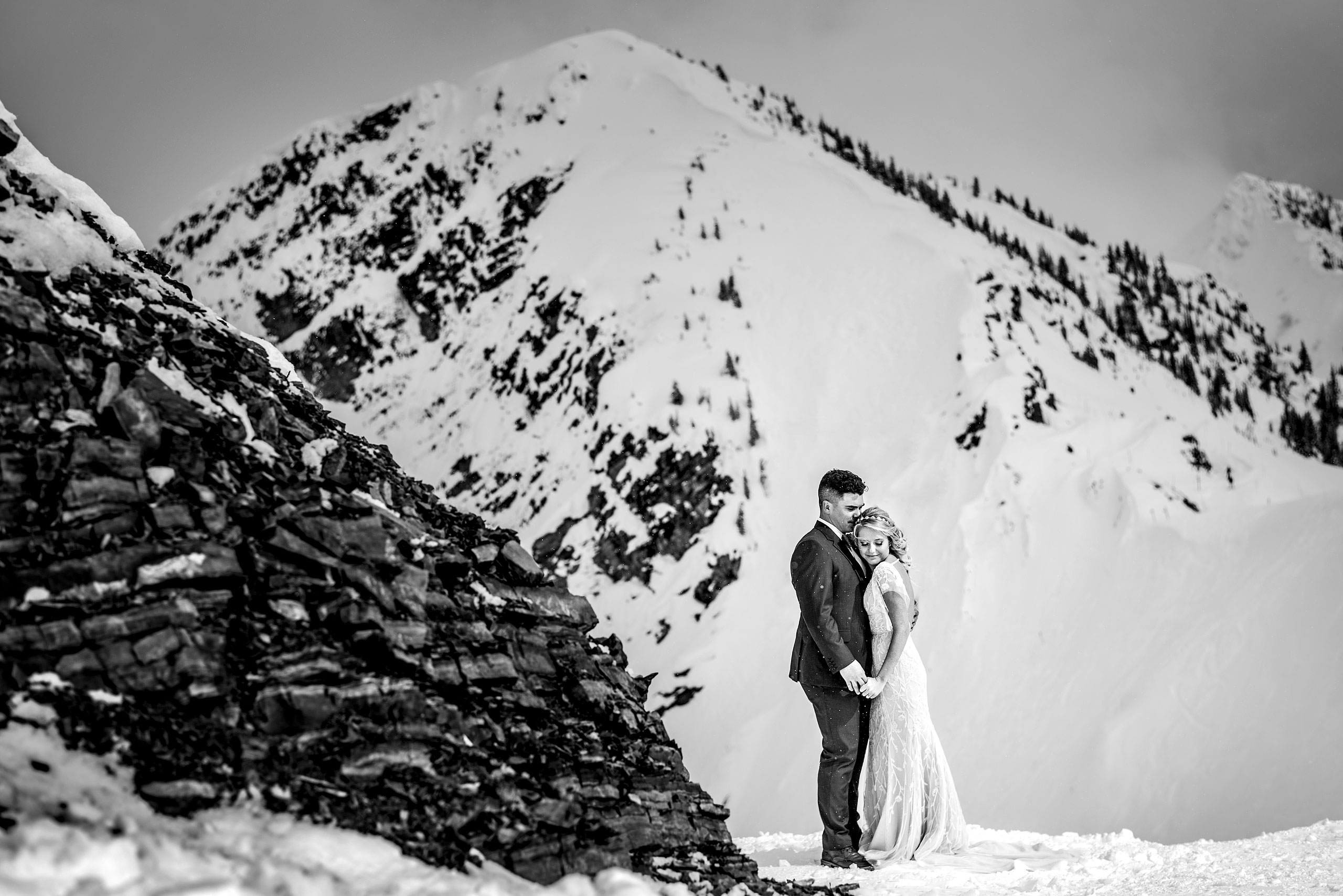 a bride and groom holding each other at a winter kicking horse wedding by sean leblanc