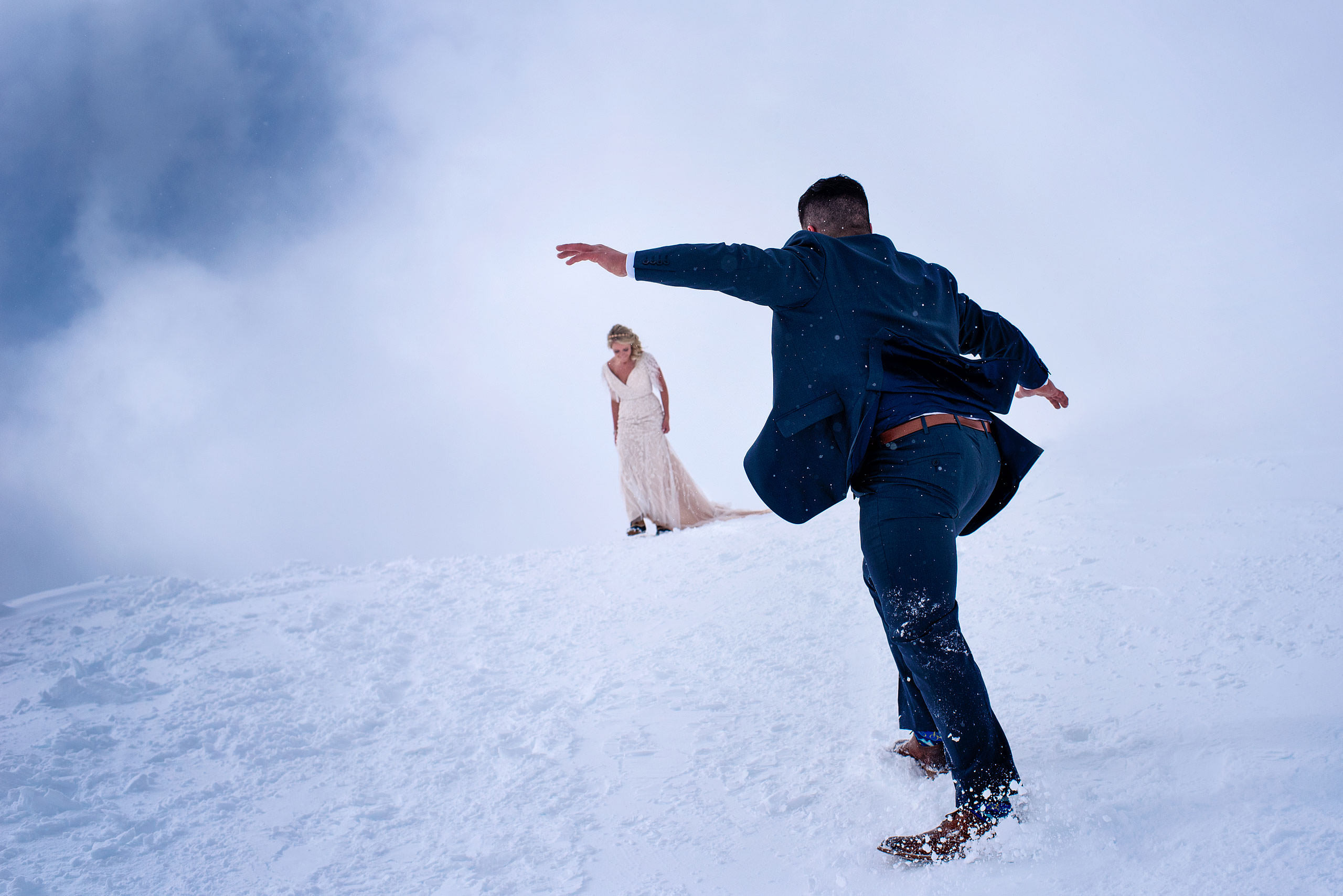 a groom sliding down a snowy hill at a winter kicking horse wedding by sean leblanc
