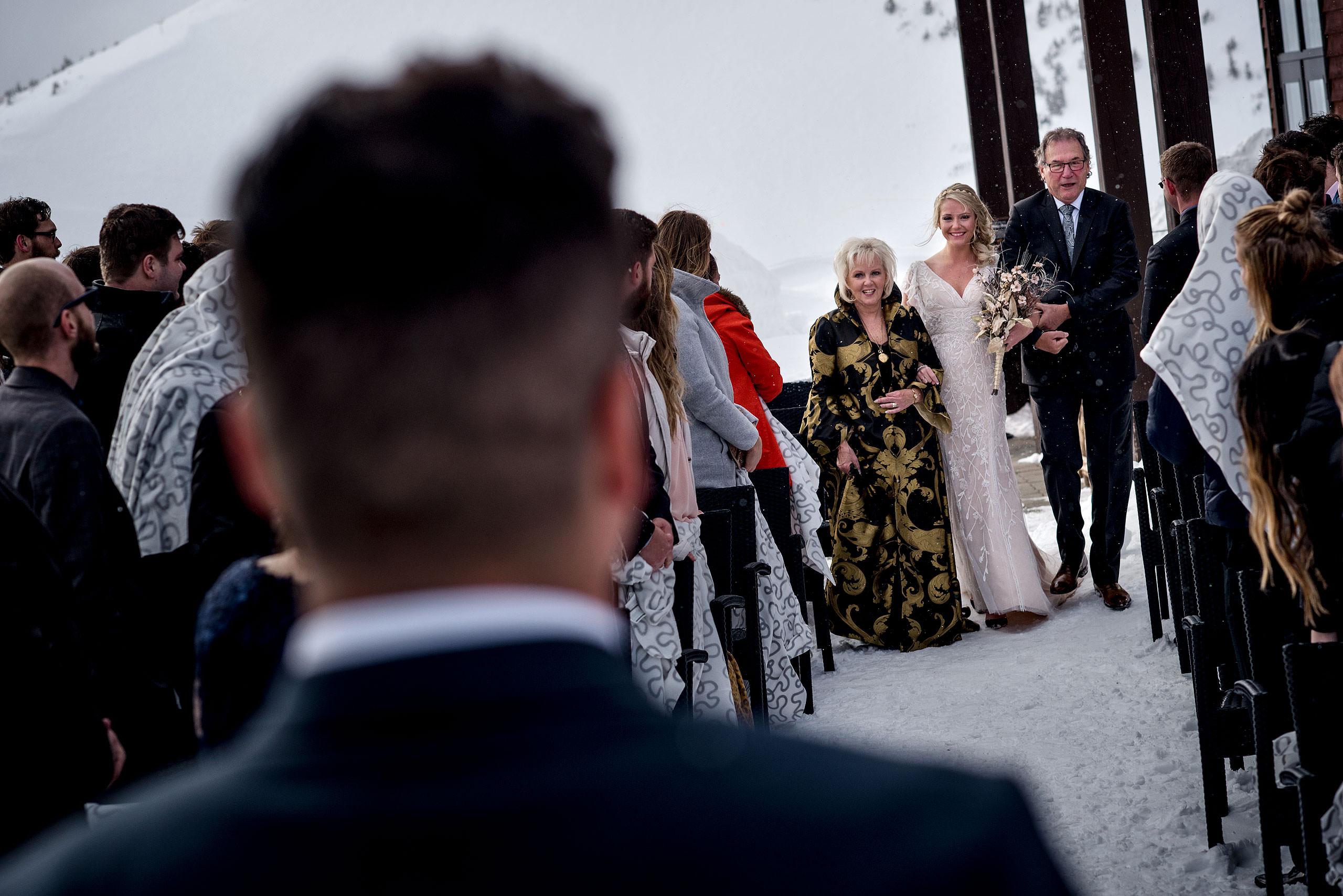 bride walking down aisle with parents at winter kicking horse wedding
