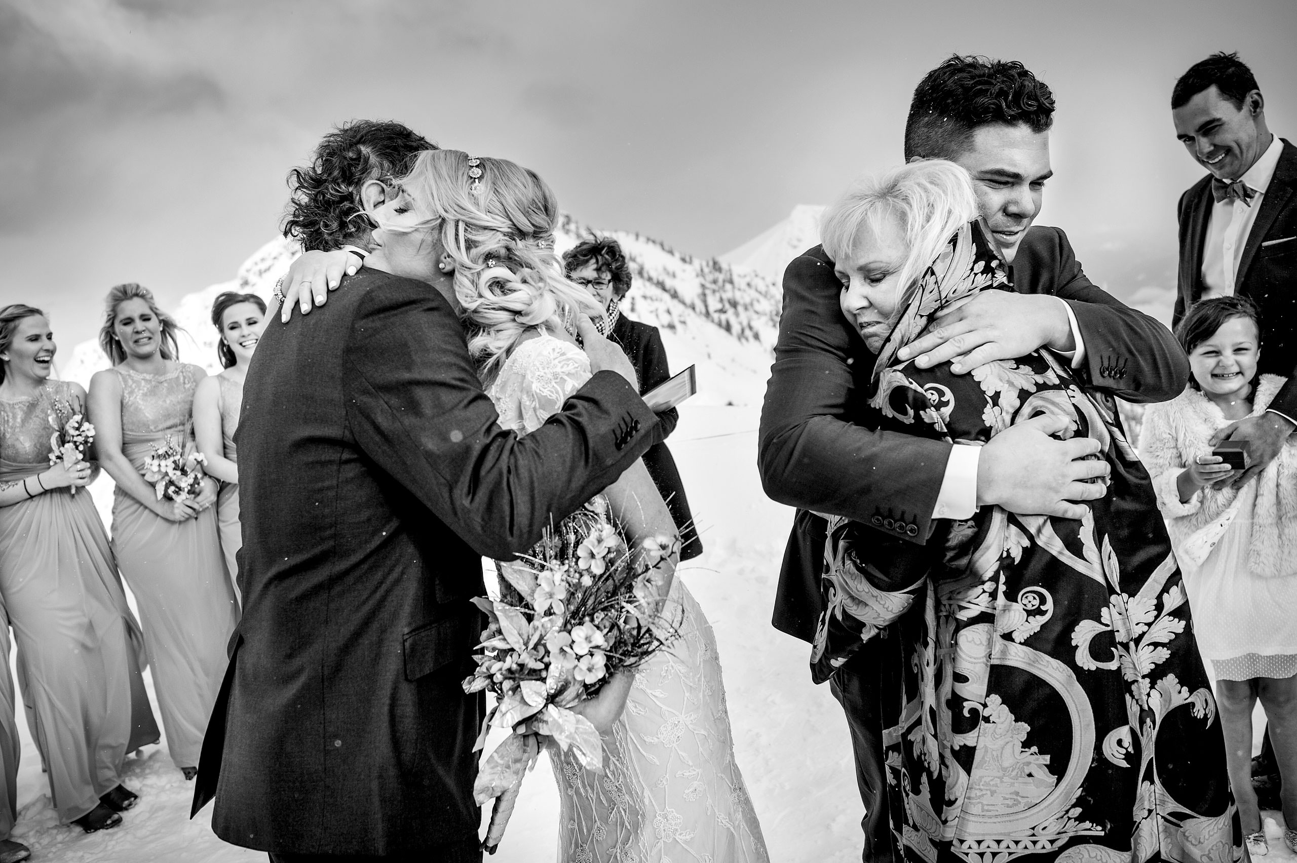 a bride and groom hugging their parents at a ceremony at a winter kicking horse wedding by sean leblanc