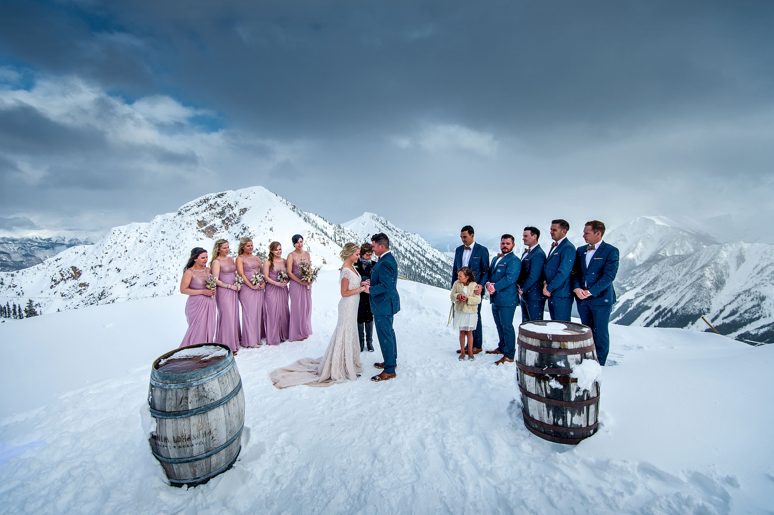 a bridal party standing at the top of a mountain at a winter kicking horse wedding by sean leblanc
