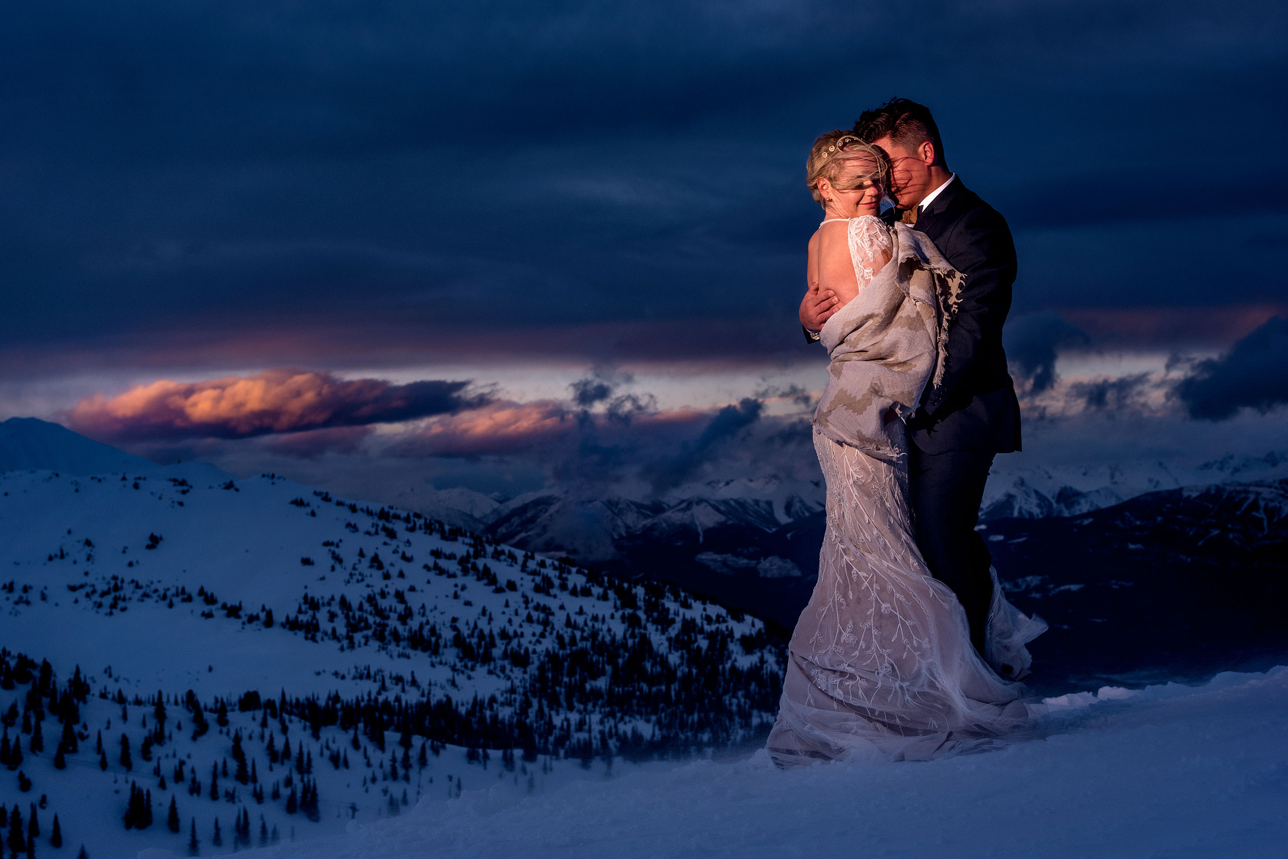 bride and groom on the top of a mountain in the winter at dusk