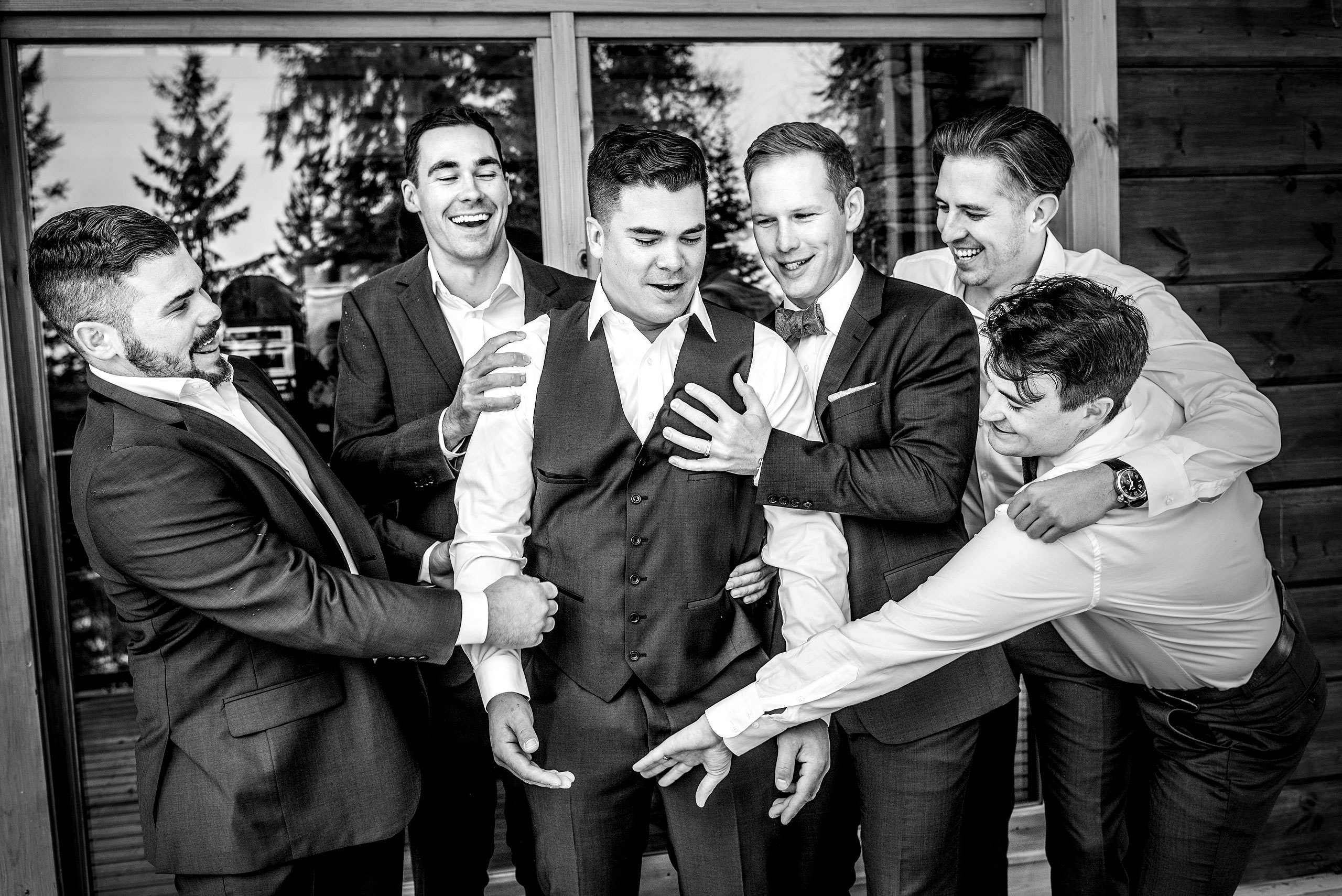 groomsmen posing on a deck at summer kicking horse wedding