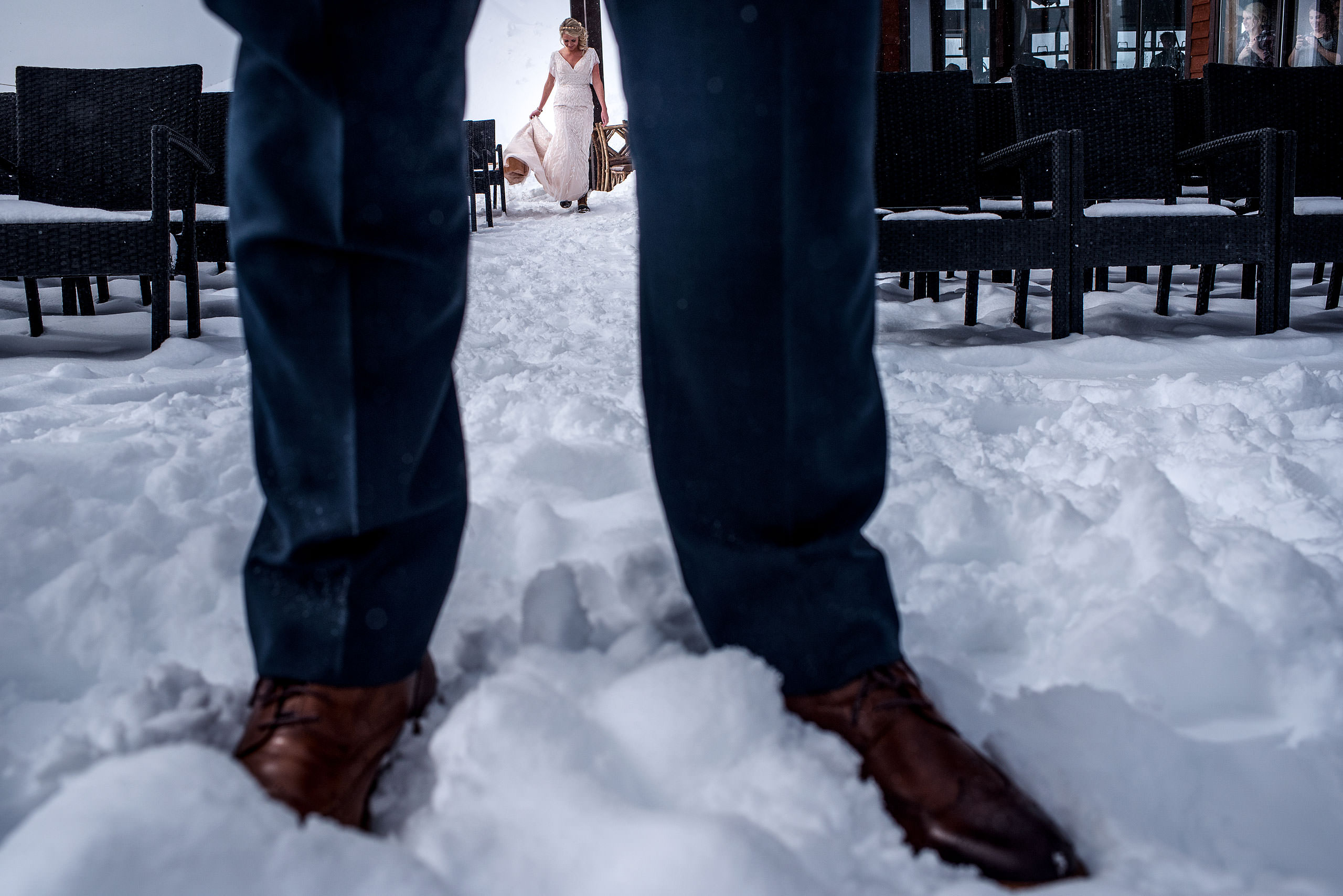 a bride framed by grooms legs at a winter kicking horse wedding by sean leblanc