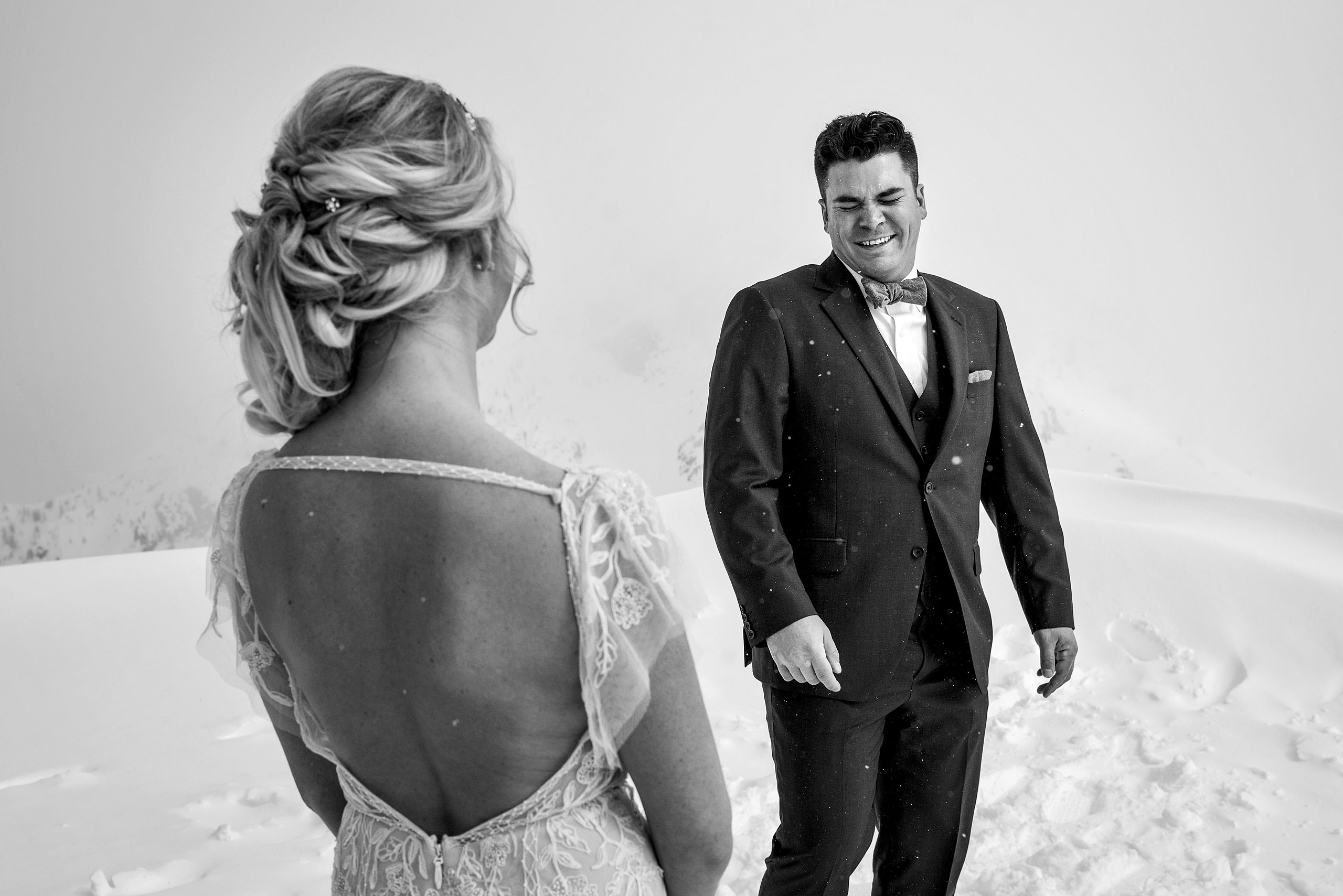 a groom crying tears of joy from seeing his bride for the first time at a winter kicking horse wedding by sean leblanc