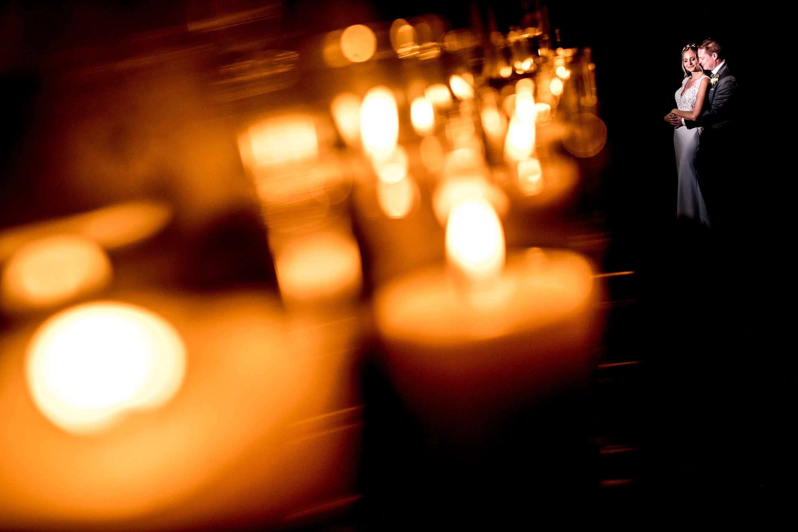 bride and groom embracing in front of a row of lit candles