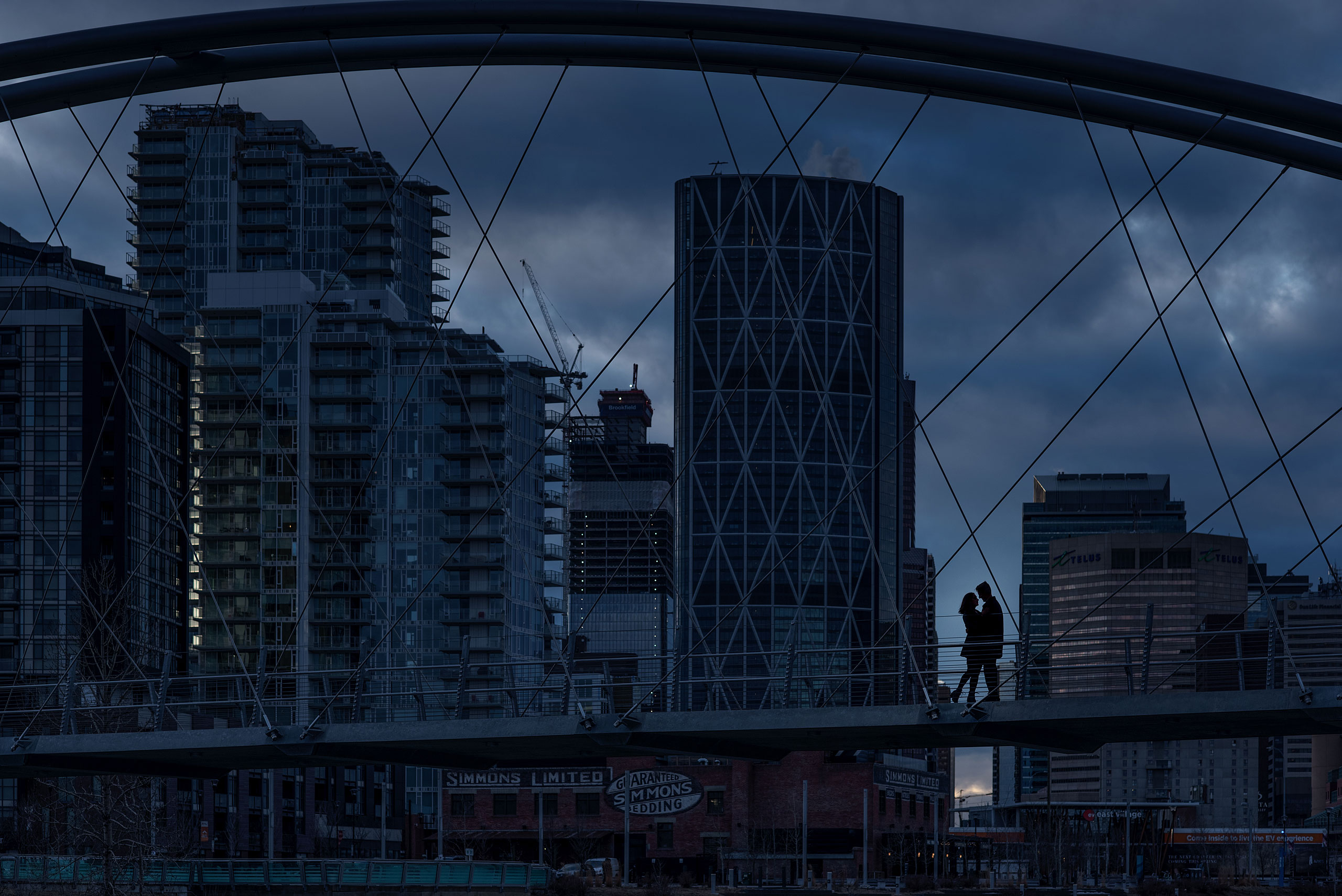 man and women silhouetted on a bridge with a city downtown skyline in the background for Calgary East Village Engagement Session