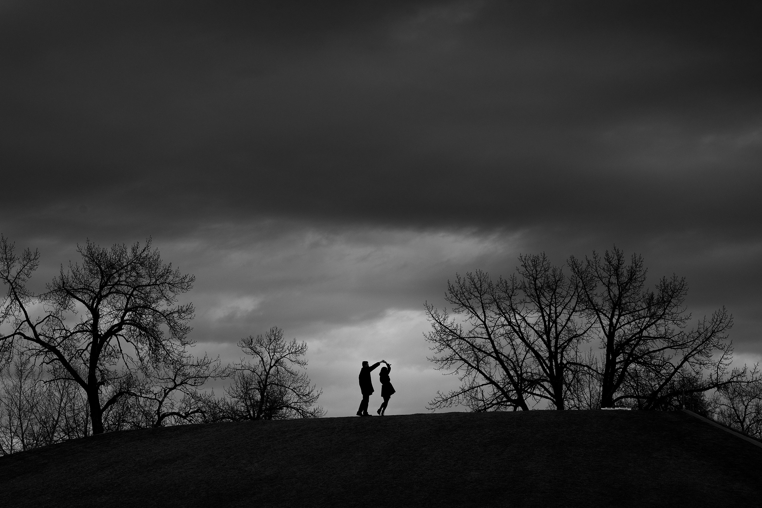 man and women dancing on the top of a hill at a Calgary East Village Engagement Session