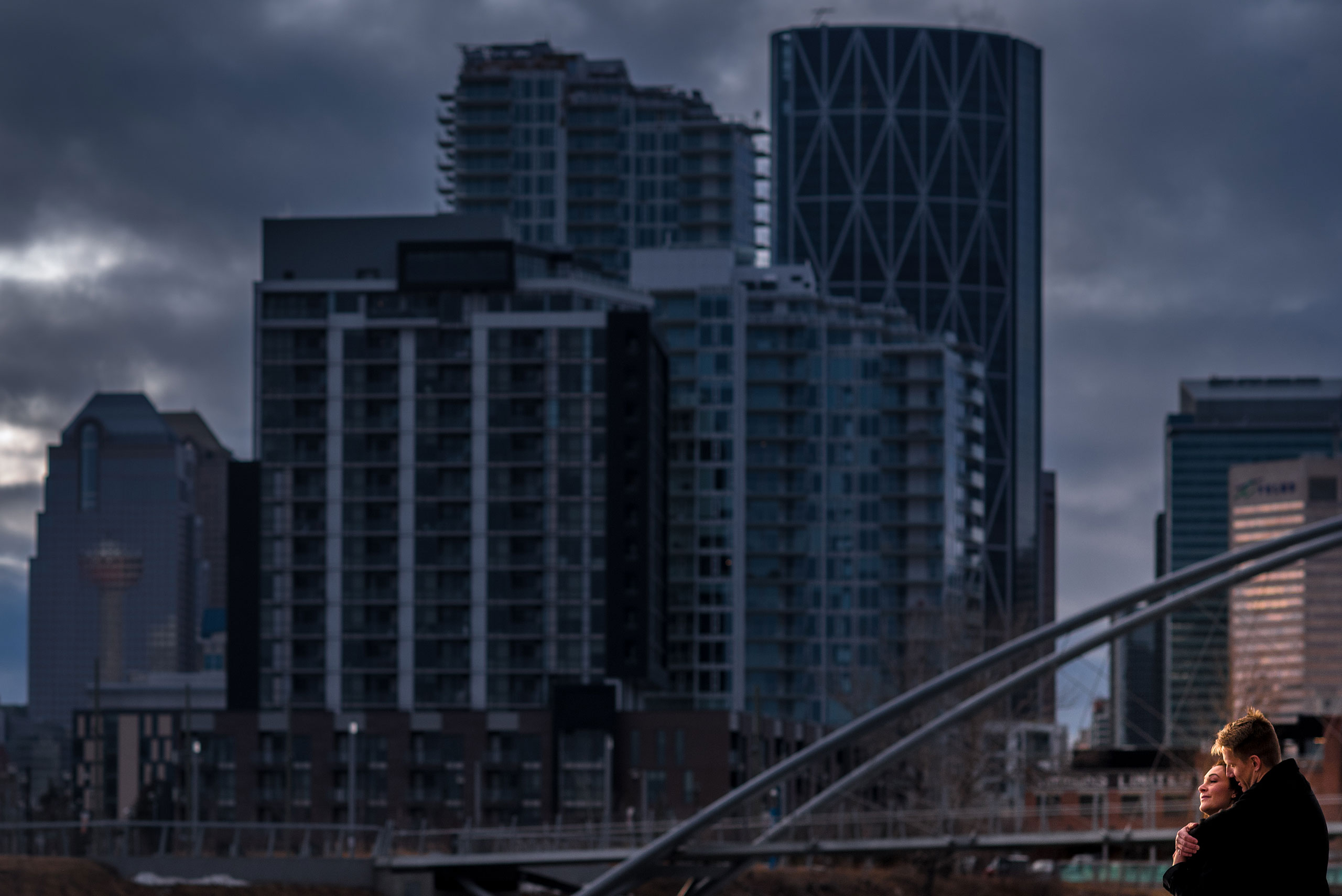 man and women on a bridge with a city downtown skyline in the background for Calgary East Village Engagement Session