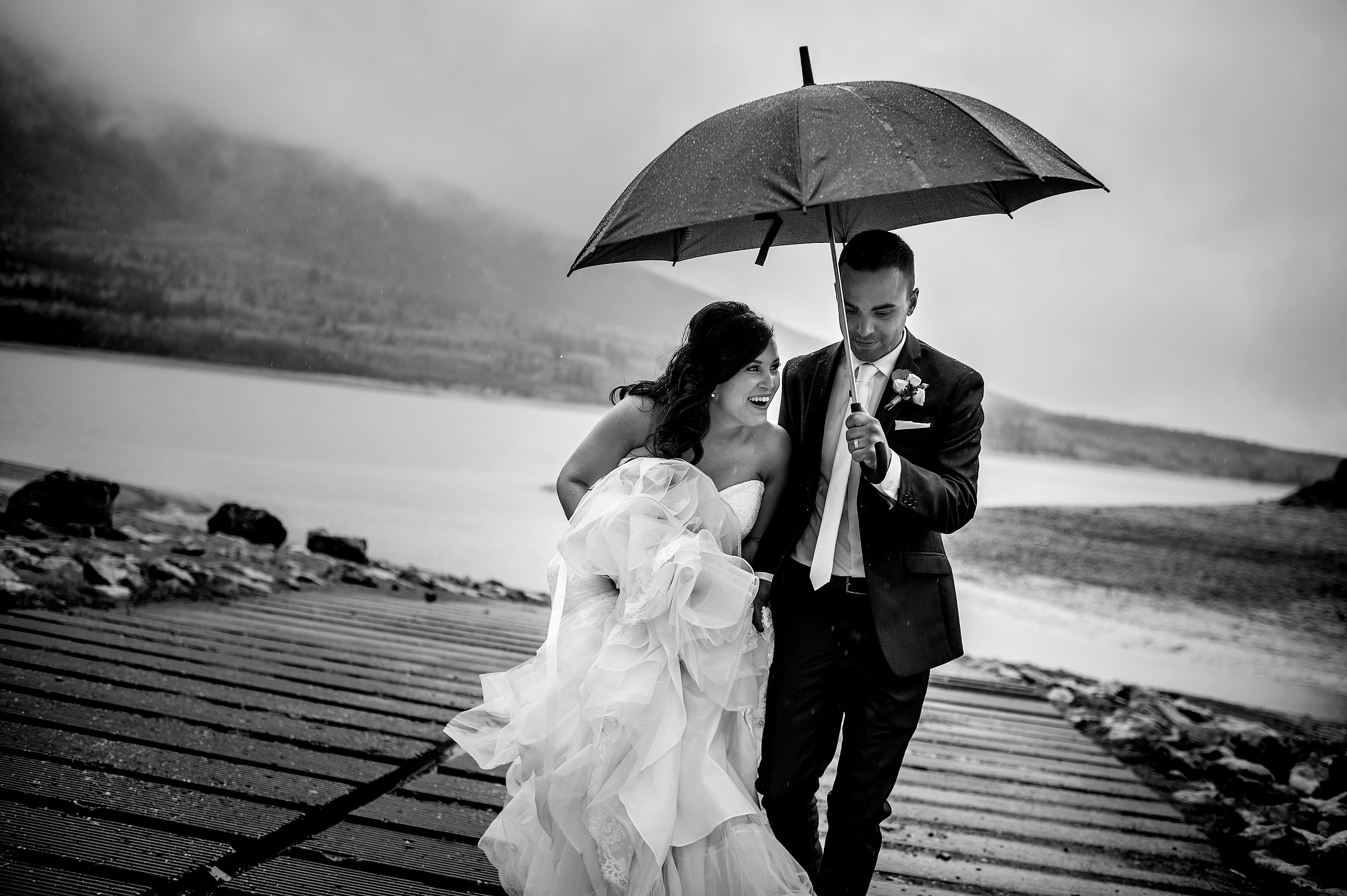a bride and groom walking up a ramp during a rainstorm by calgary wedding photographers
