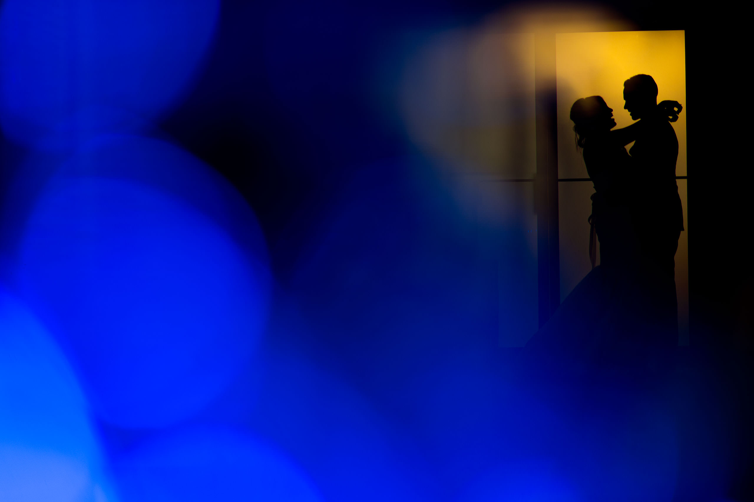 silhouette of bride and groom posing in front of warm color window by top calgary wedding photographer sean leblanc
