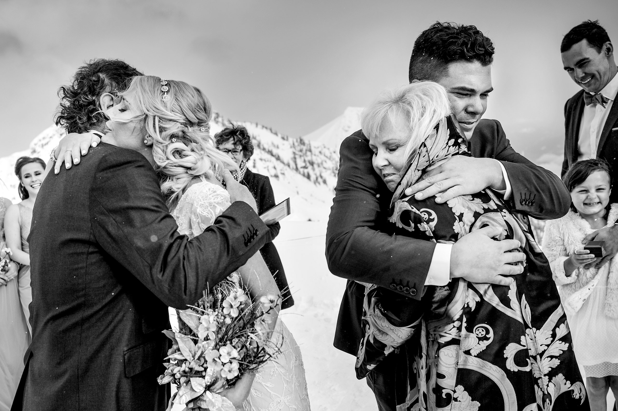 a groom hugging his mom and a bride hugging her dad at winter kicking horse wedding