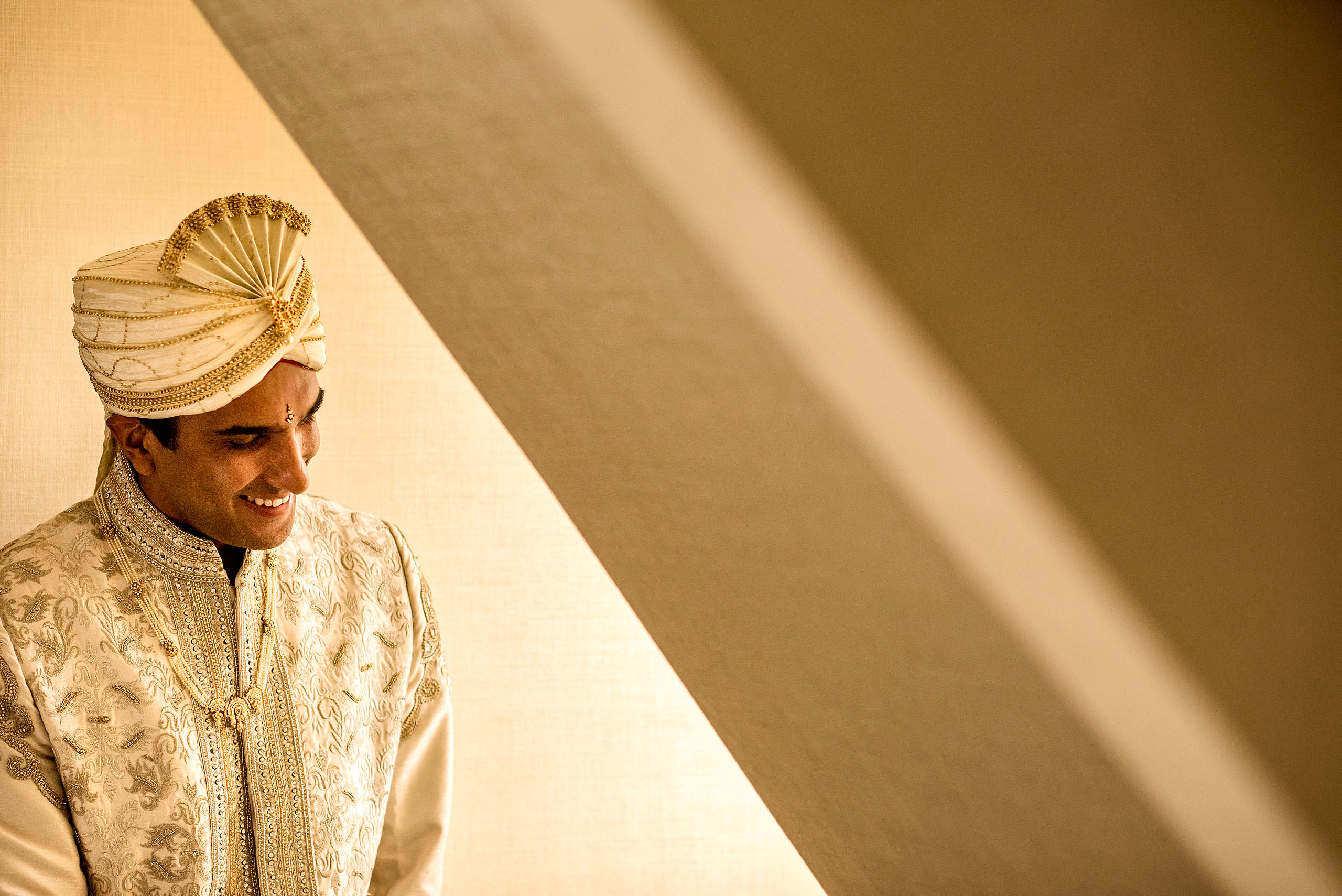 indian groom laughing by a winder for cascade ballroom banff springs wedding by sean leblanc