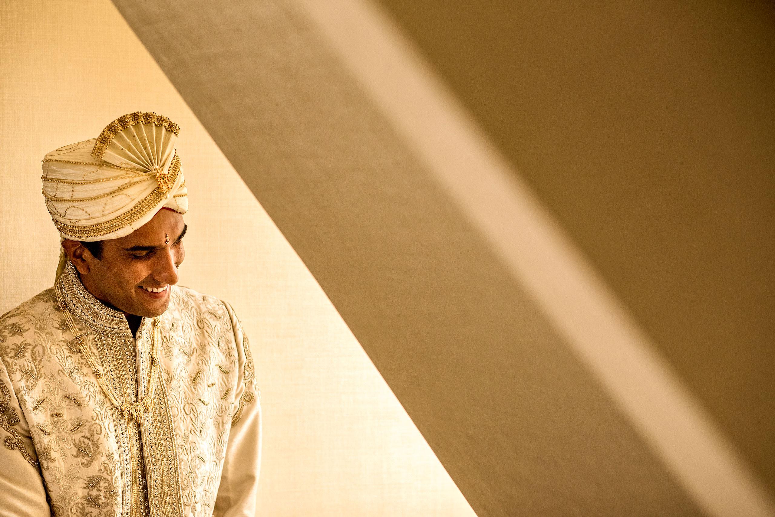 indian groom laughing by a winder for cascade ballroom banff springs wedding by sean leblanc