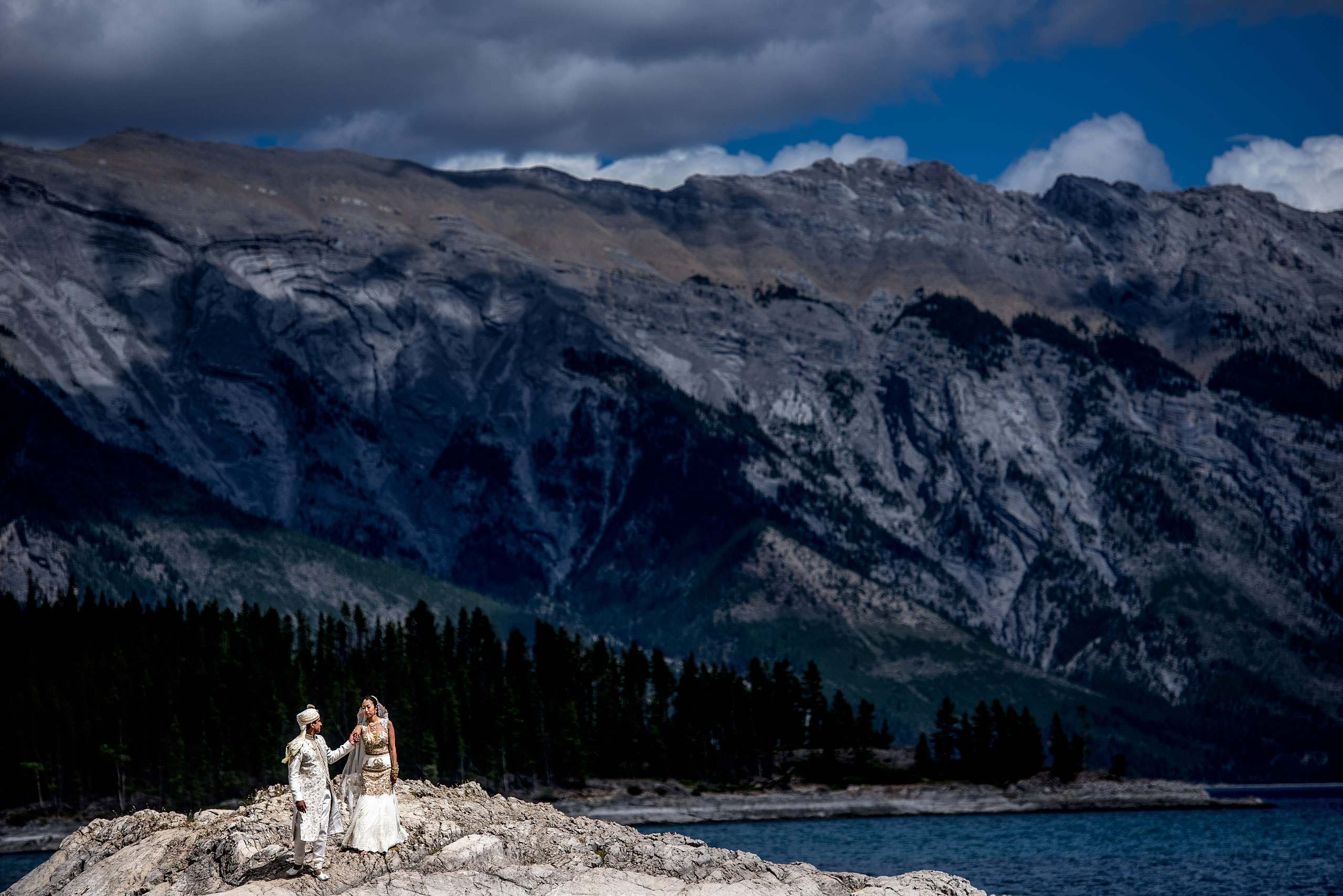 indian groom leading his bride down a mountain by Banff wedding photographer