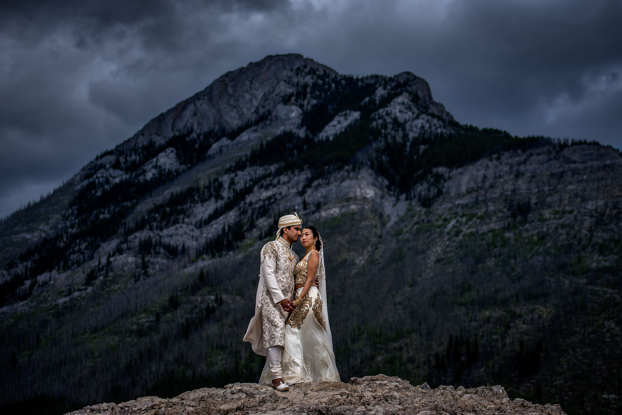 Indian bride and groom wearing traditional Indian wedding clothing embracing on top of a mountain