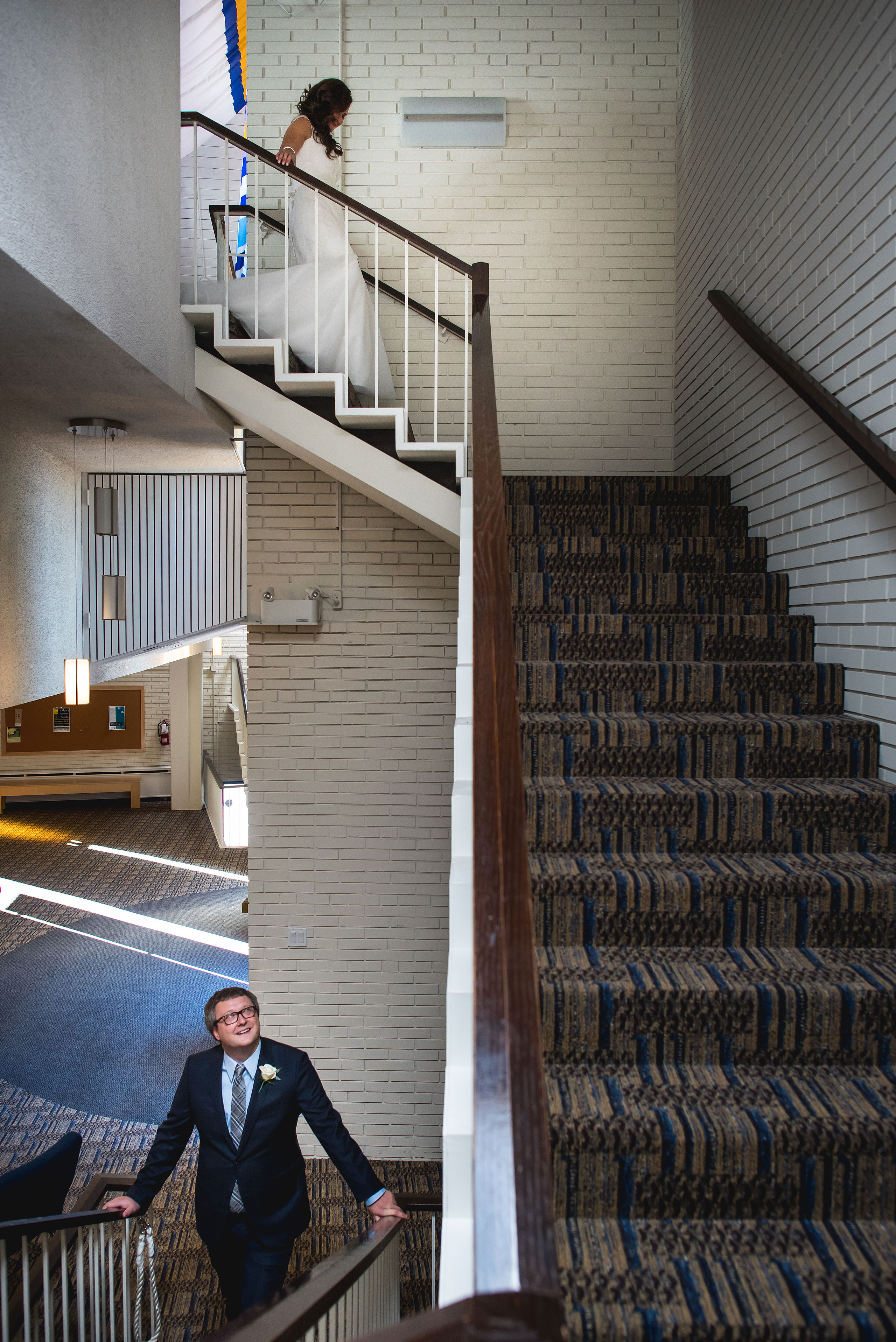 a bride walking down stairs to meet her groom by Calgary Jewish Wedding Photographer Sean LeBlanc