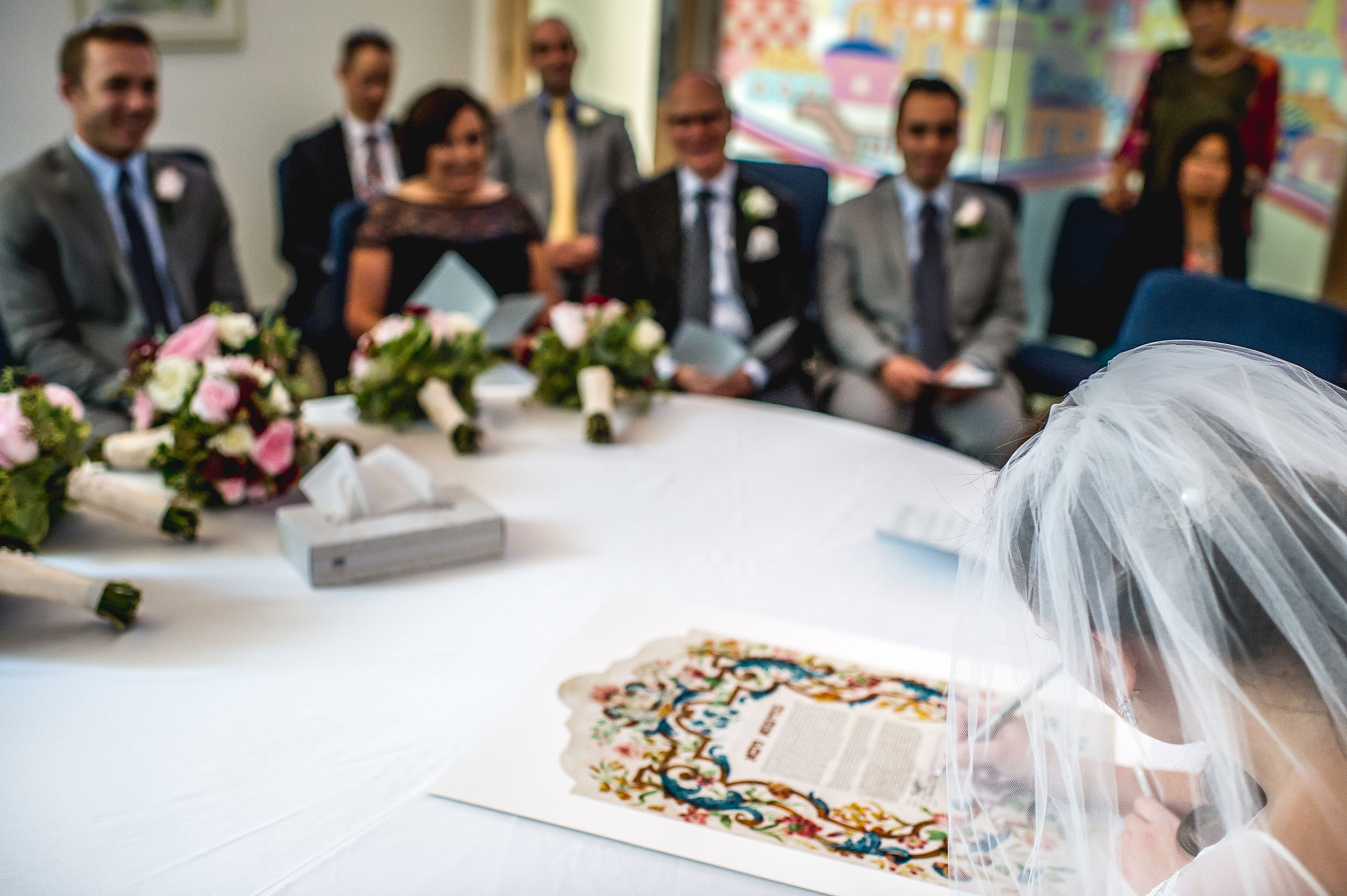 a bride writing on a document by Calgary Jewish Wedding Photographer Sean LeBlanc