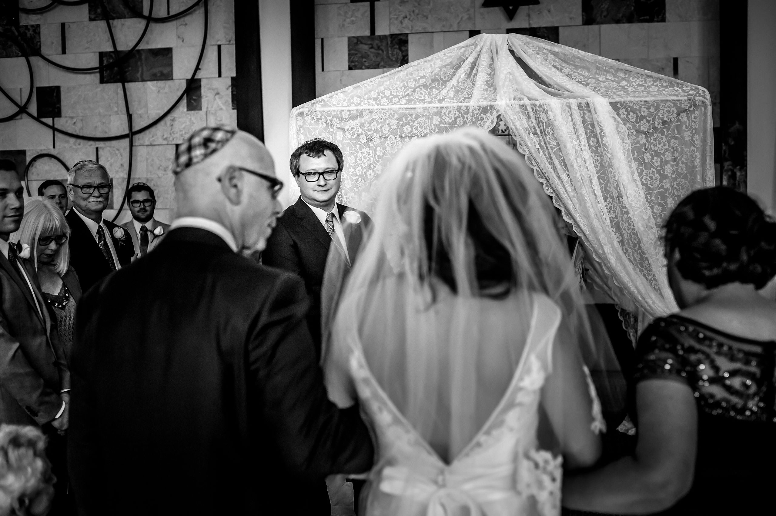 a bride walking down the aisle with her parents by Calgary Jewish Wedding Photographer Sean LeBlanc