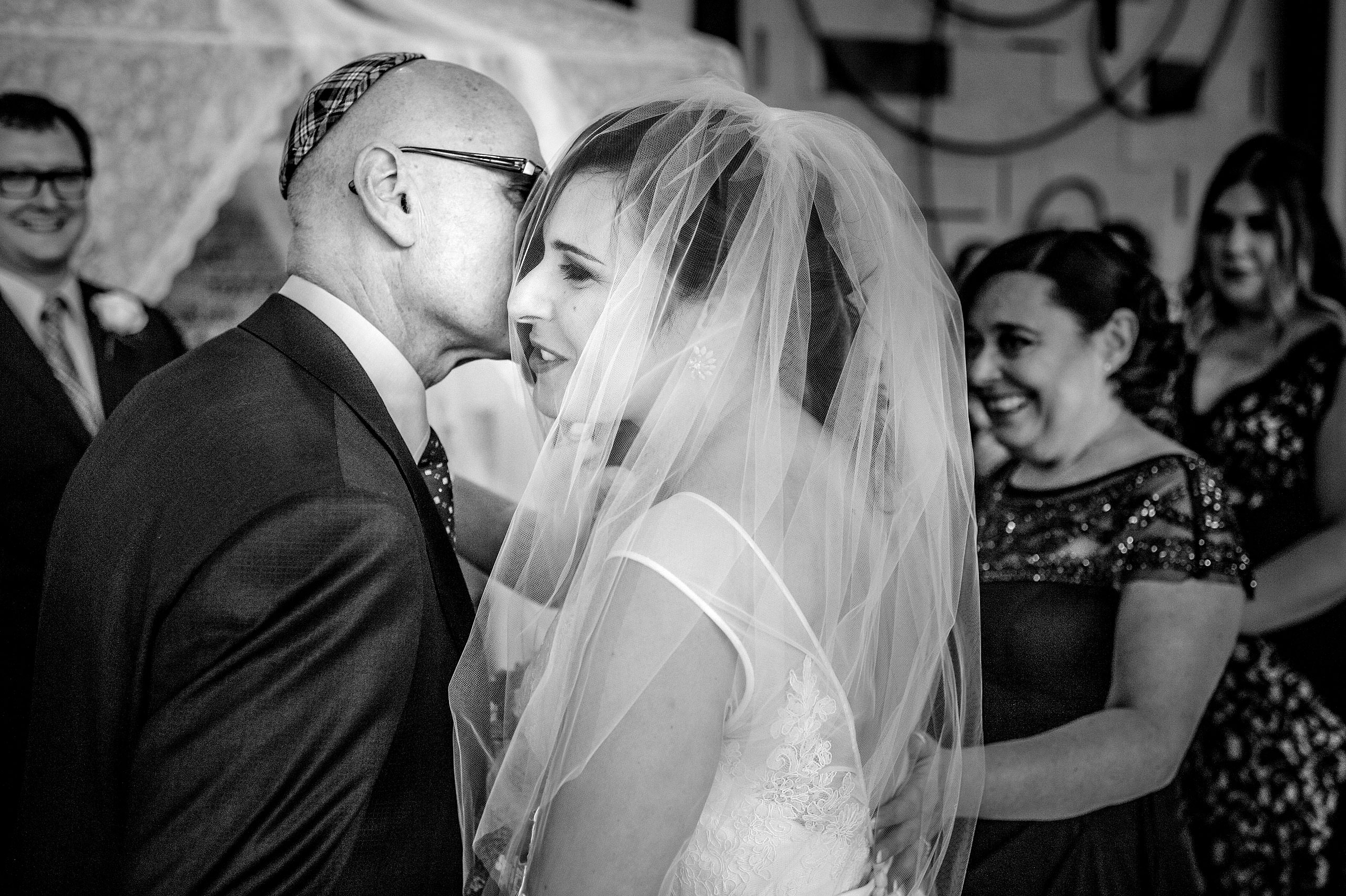 a father kissing his daughter by Calgary Jewish Wedding Photographer Sean LeBlanc