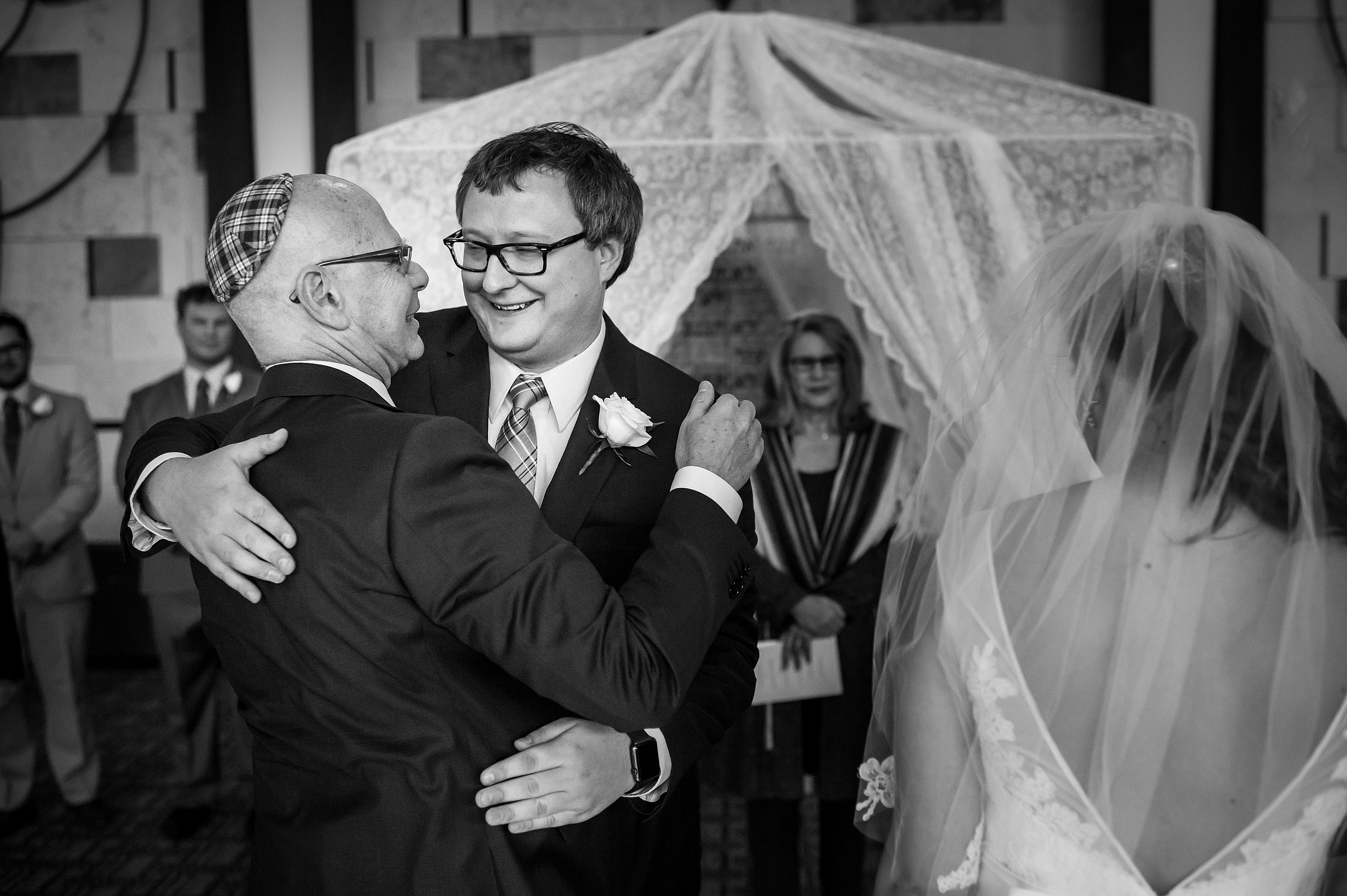 a groom hugging a bride's dad by Calgary Jewish Wedding Photographer Sean LeBlanc