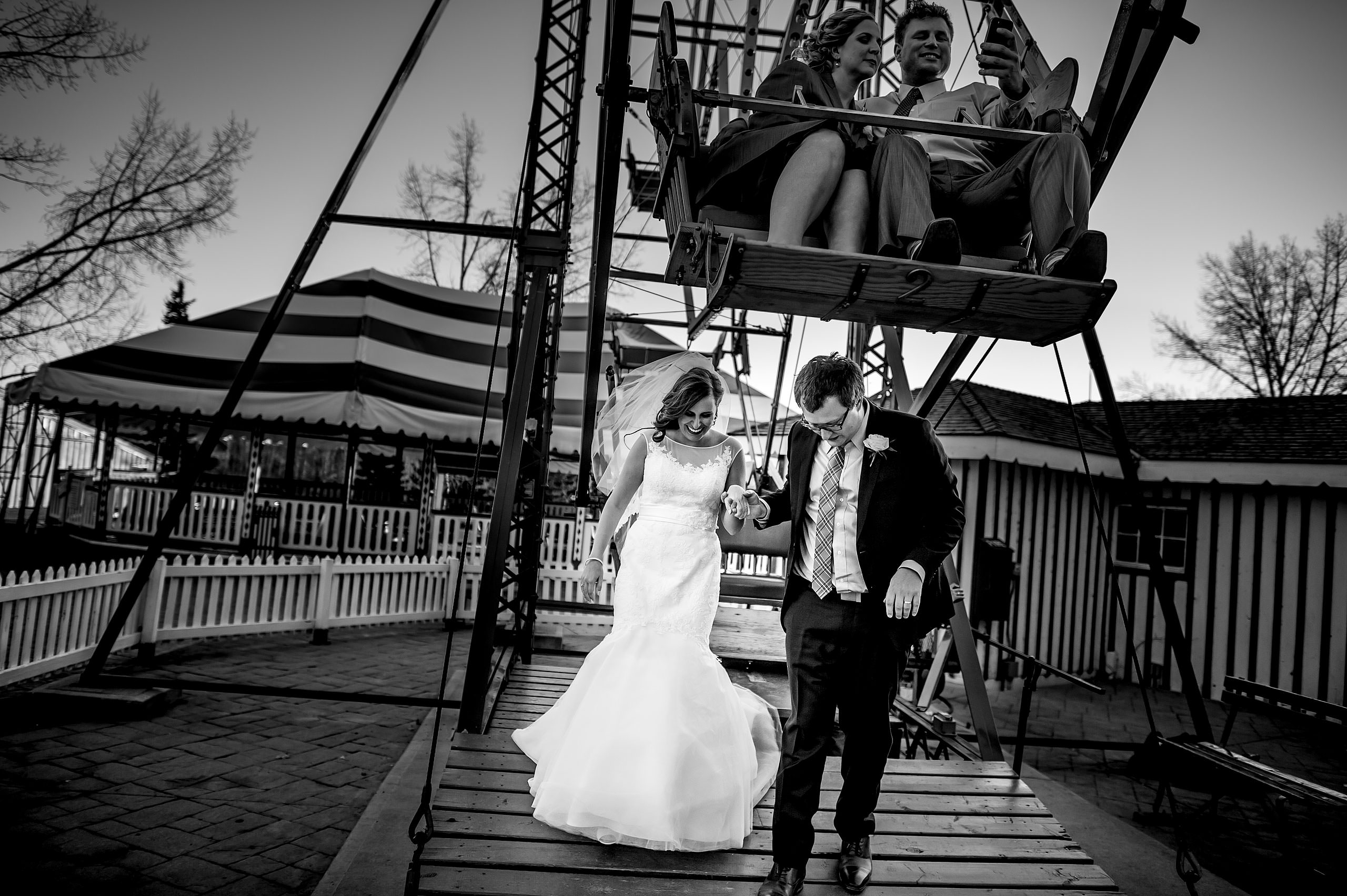 a bride and groom walking away from a Ferris wheel by Calgary Jewish Wedding Photographer Sean LeBlanc