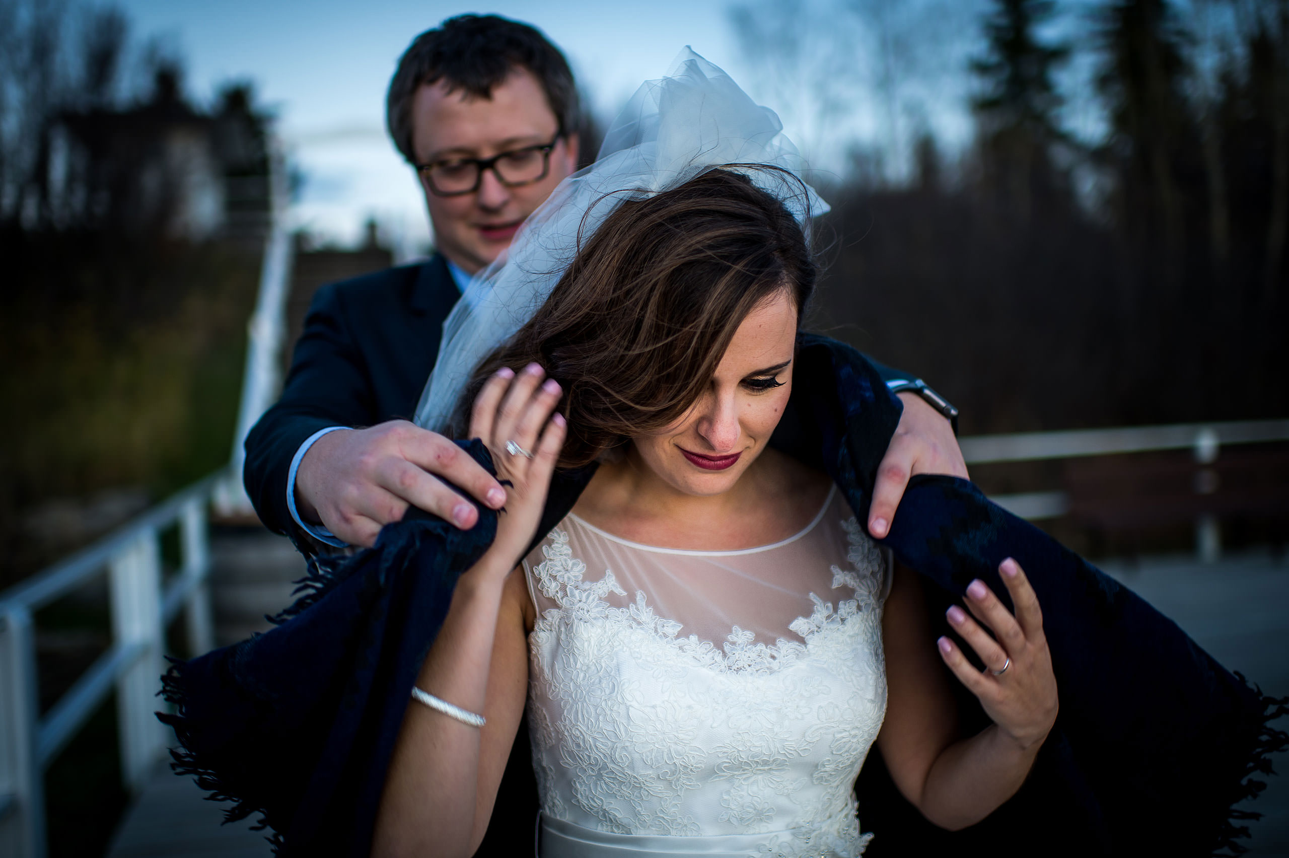 a groom offering his jacket to his bride by Calgary Jewish Wedding Photographer Sean LeBlanc