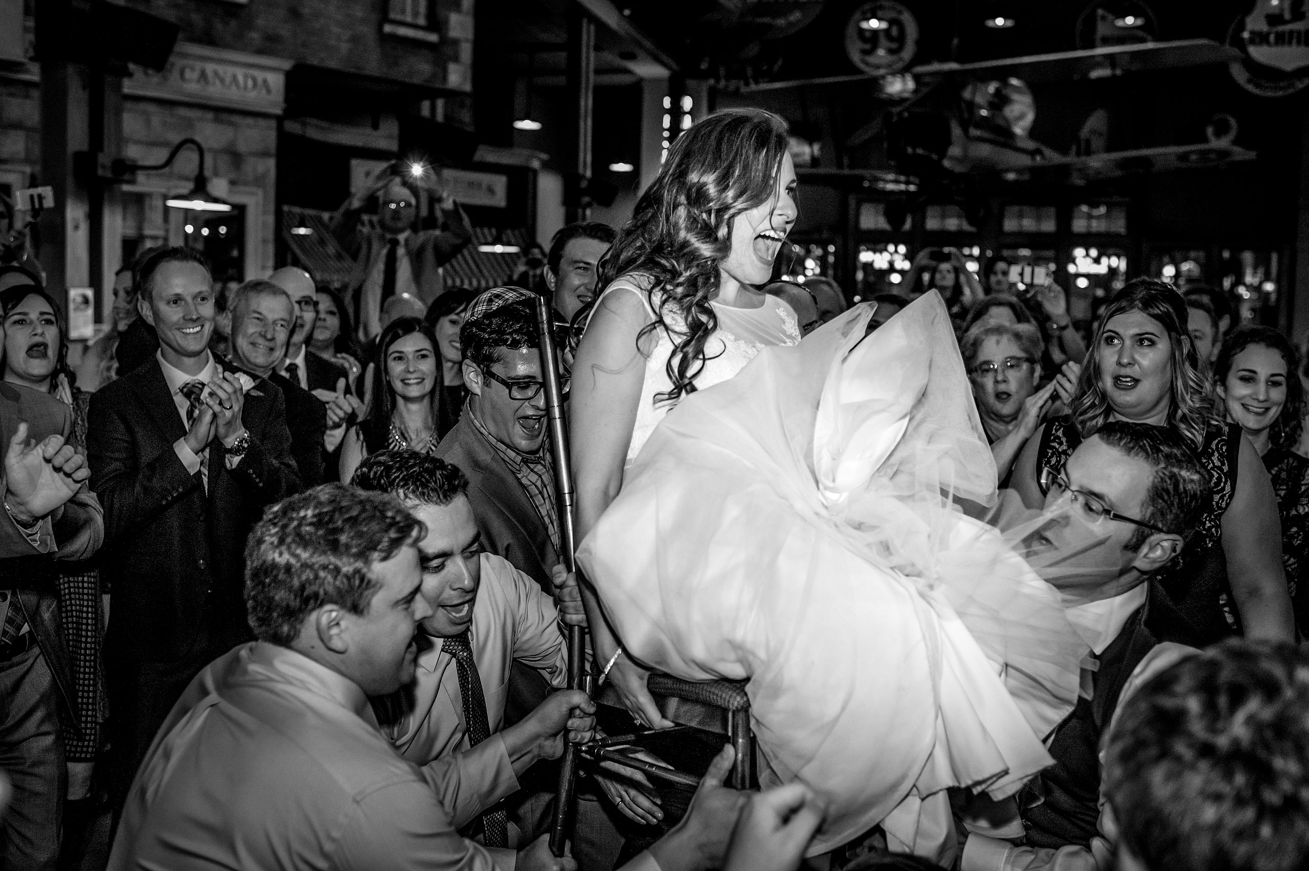 a bride being lifted on a chair at a reception by Calgary Jewish Wedding Photographer Sean LeBlanc