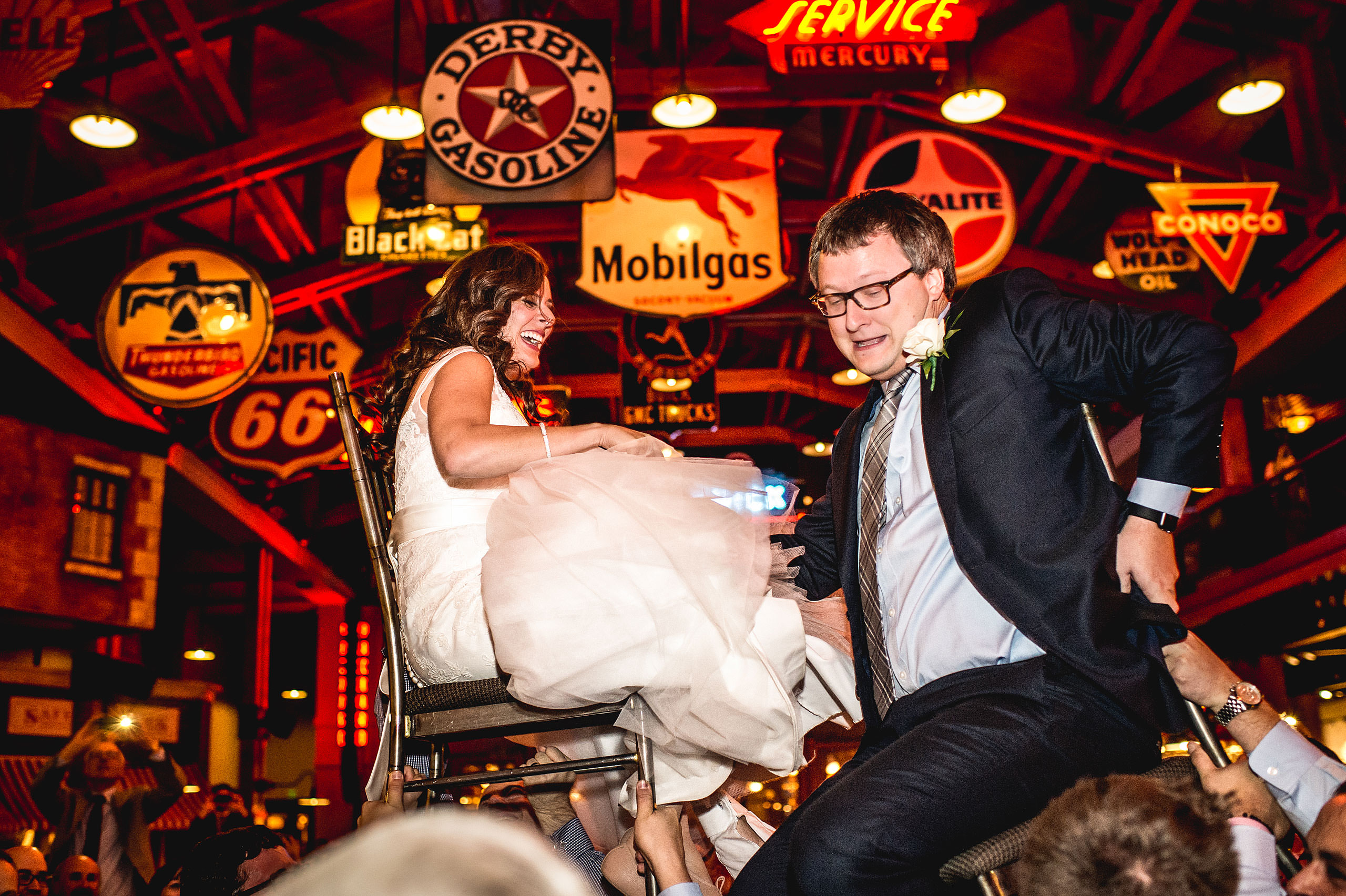 a bride and groom being lifted on chairs by Calgary Jewish Wedding Photographer Sean LeBlanc