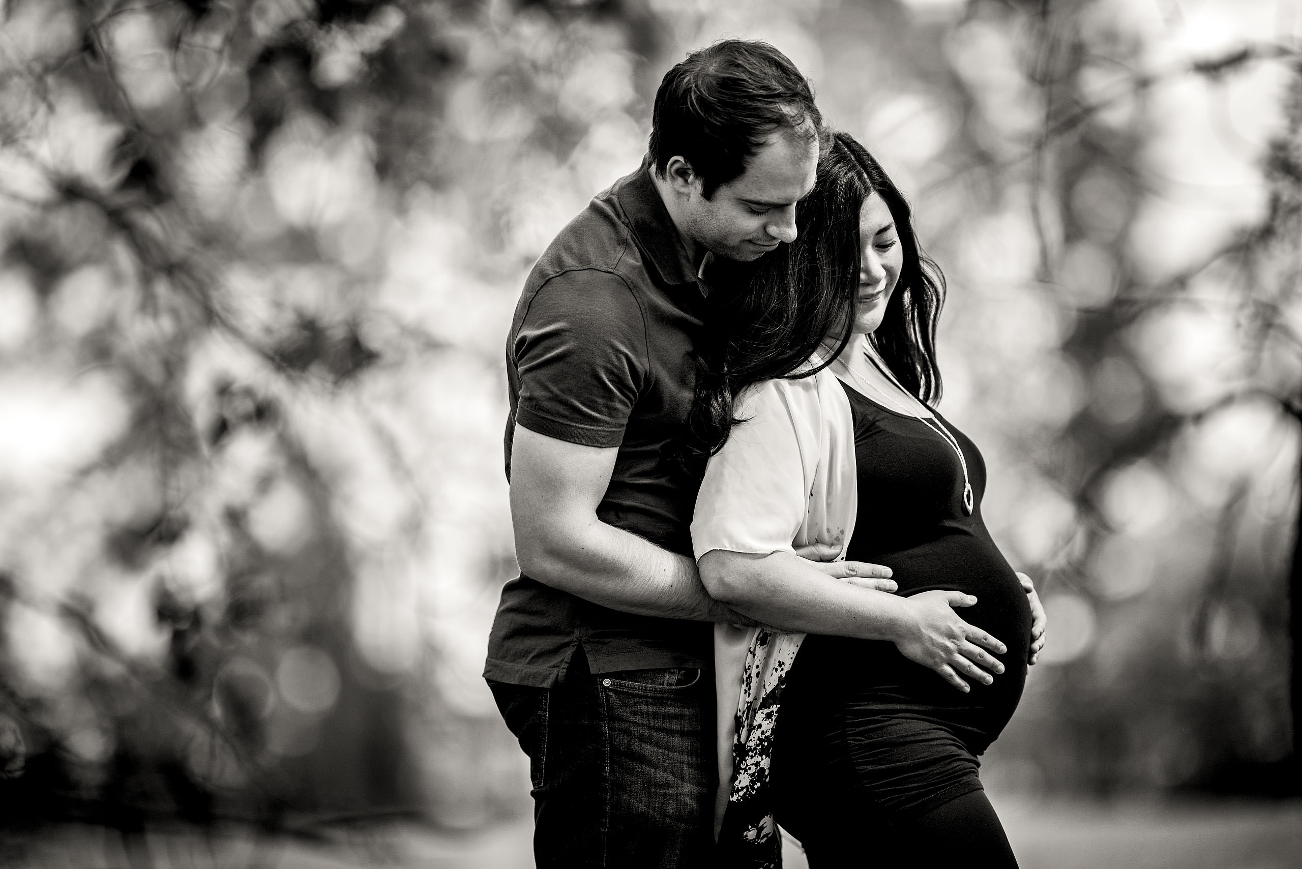 a pregnant women being embraced by her partner under a tree by top family portrait photographer sean leblanc