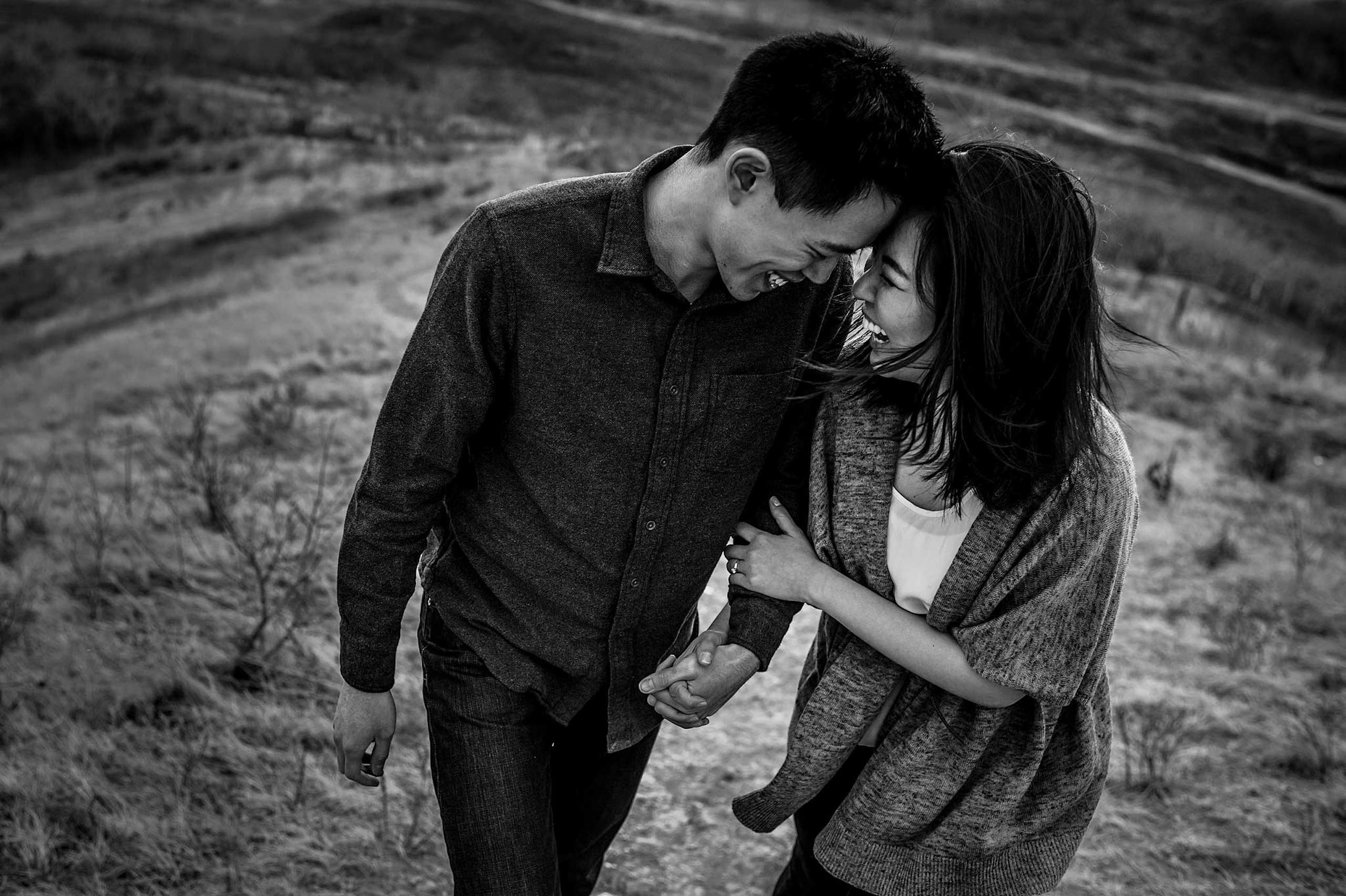 a man and his fiancé walking up a hill together by top calgary engagement photographer sean leblanc