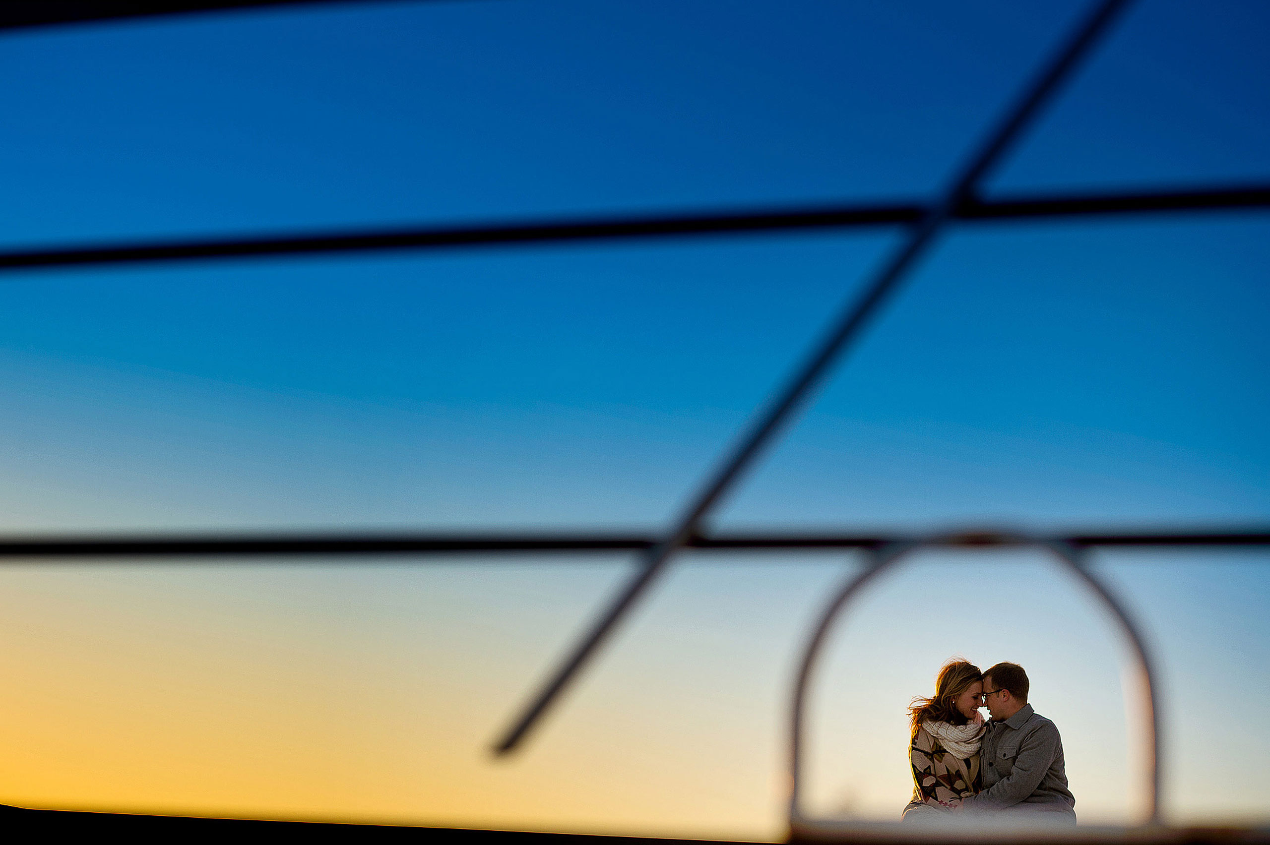 a man and his fiancé gazing into each others eyes in front of a fence by top calgary engagement photographer sean leblanc