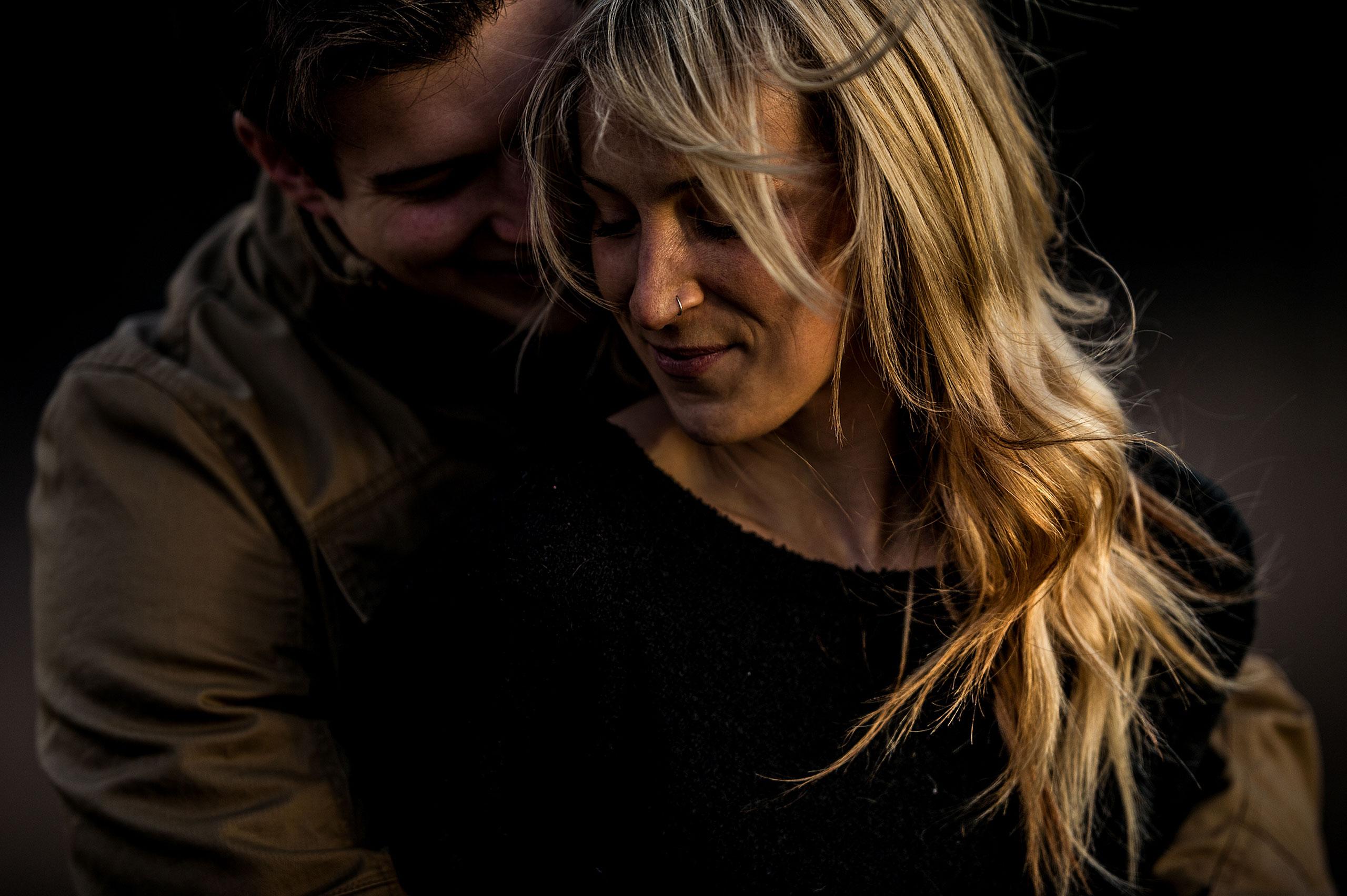 a man whispering into his fiancés ear by top calgary engagement photographer sean leblanc