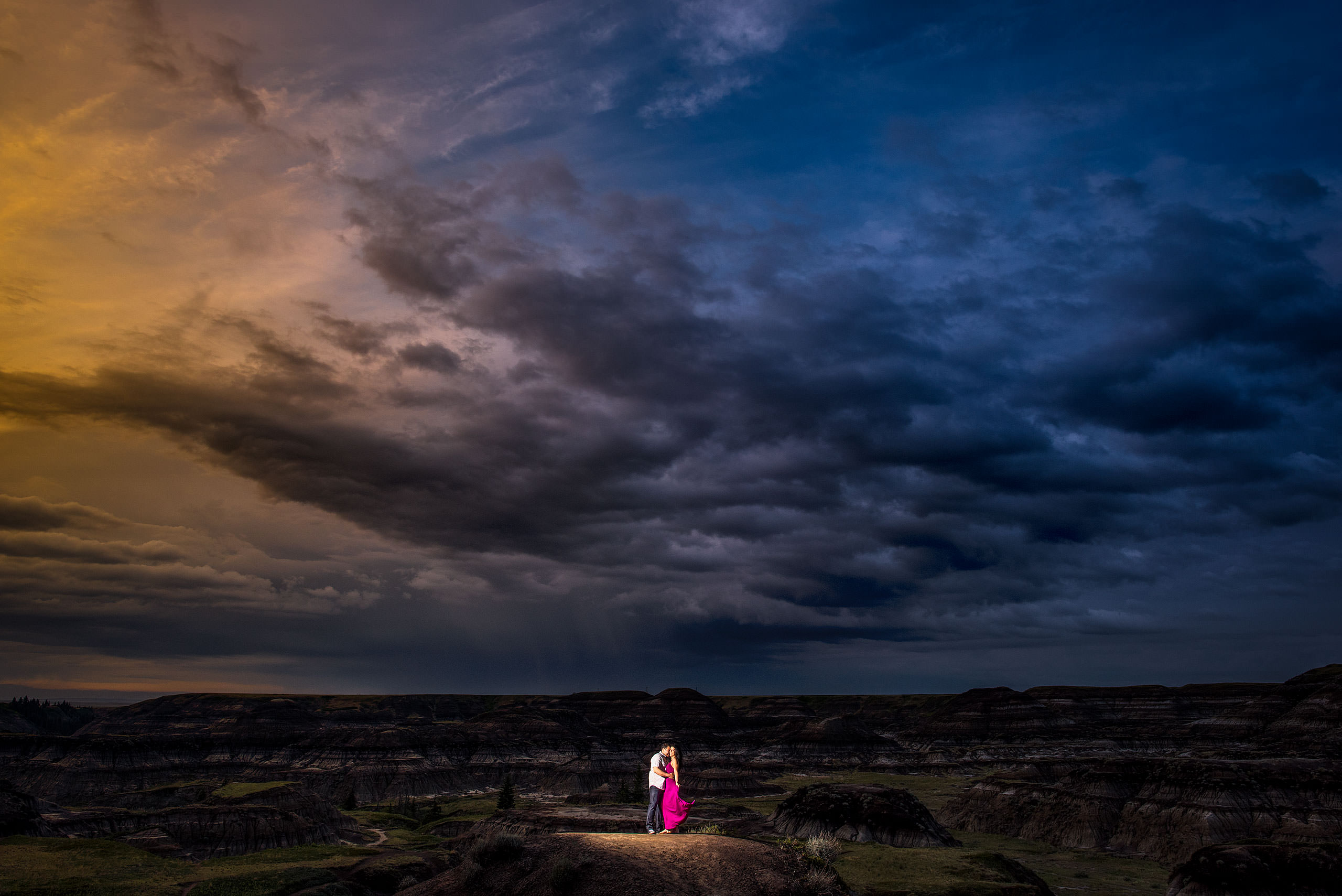 a man and girl wearing a pink dress posing in a canyon at dusk - drumheller engagement session