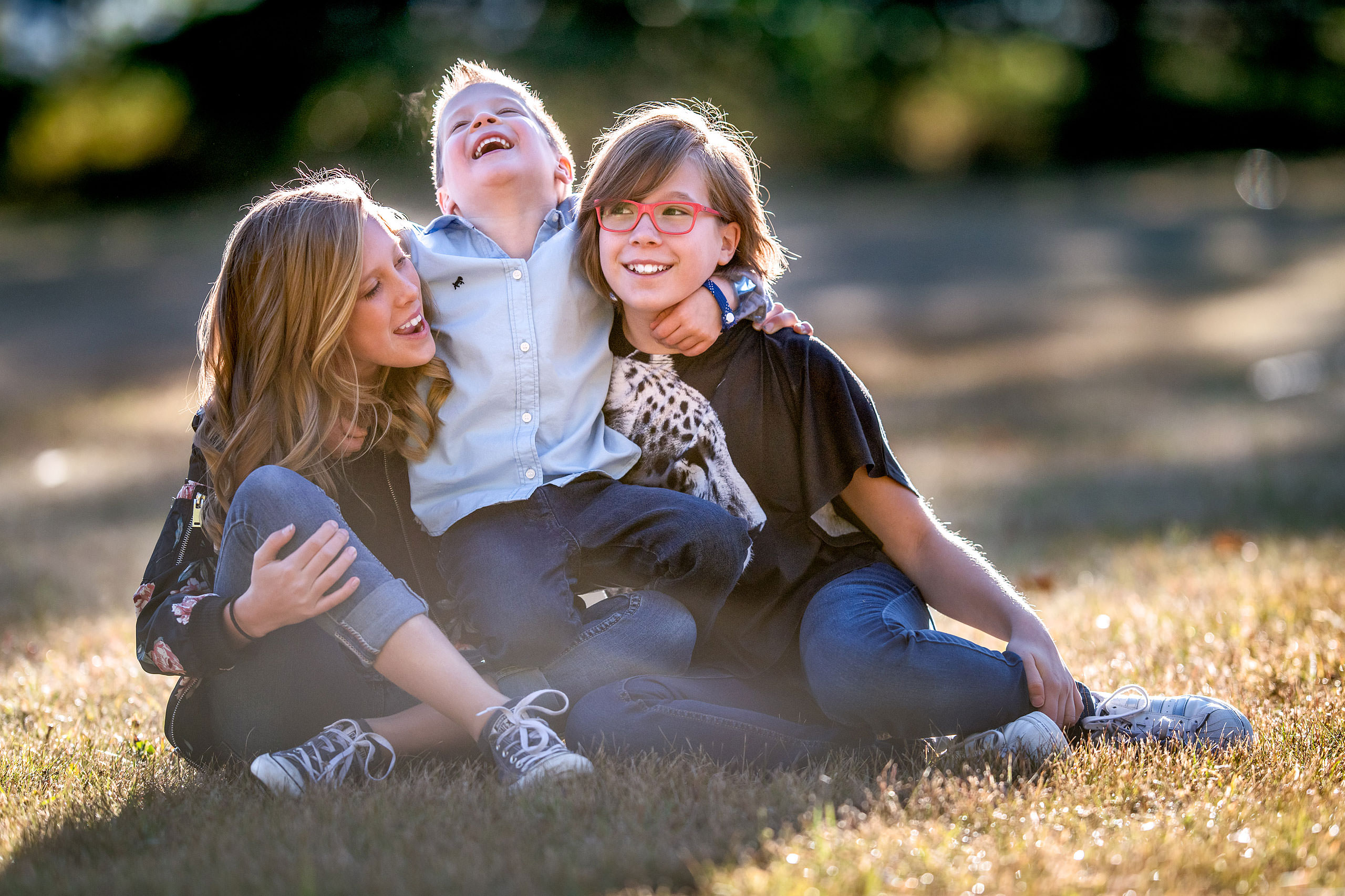 three young kids sitting on the grass laughing together by top family portrait photographer sean leblanc