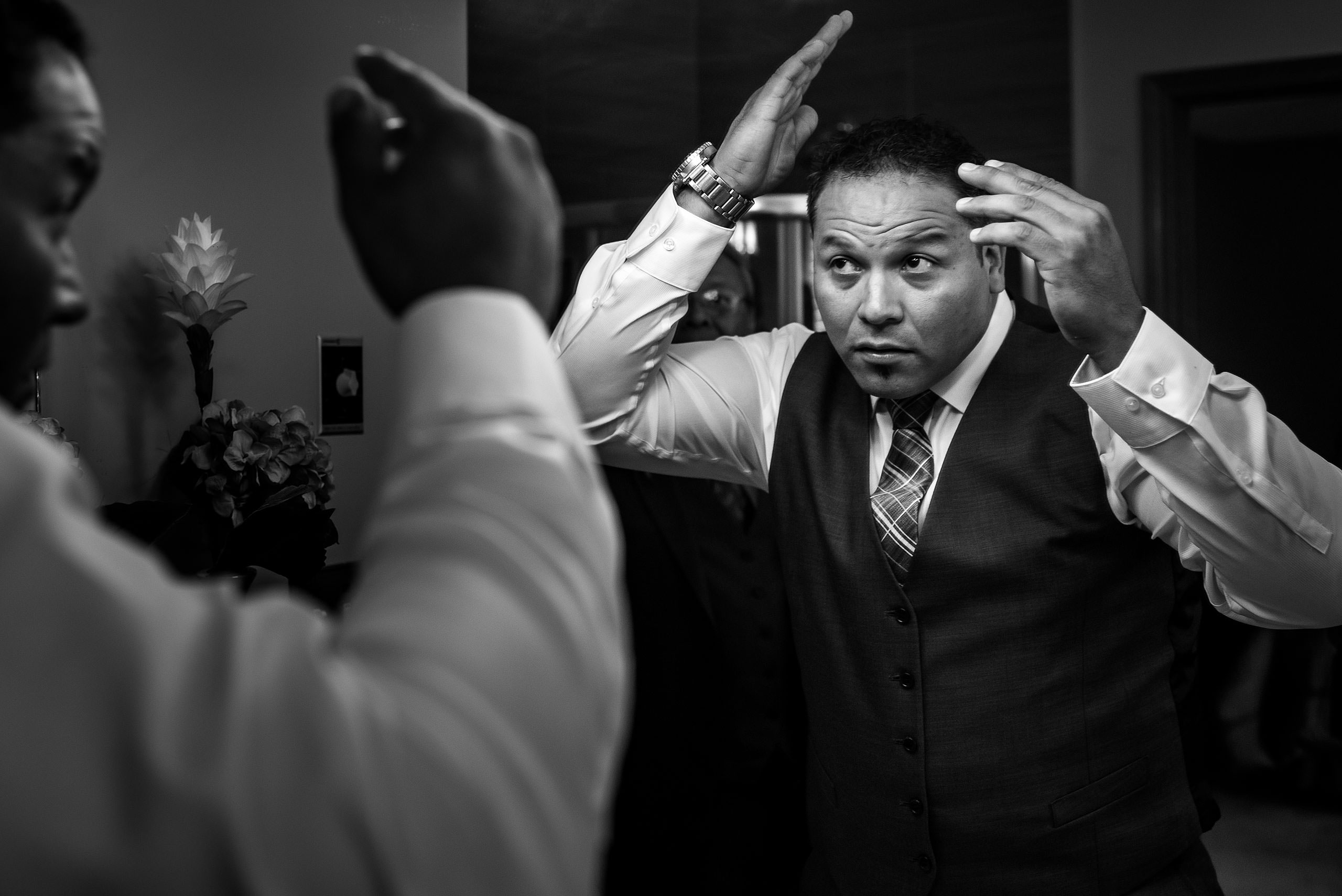 A groom getting ready by combing his hair by Edmonton wedding photographer sean leblanc