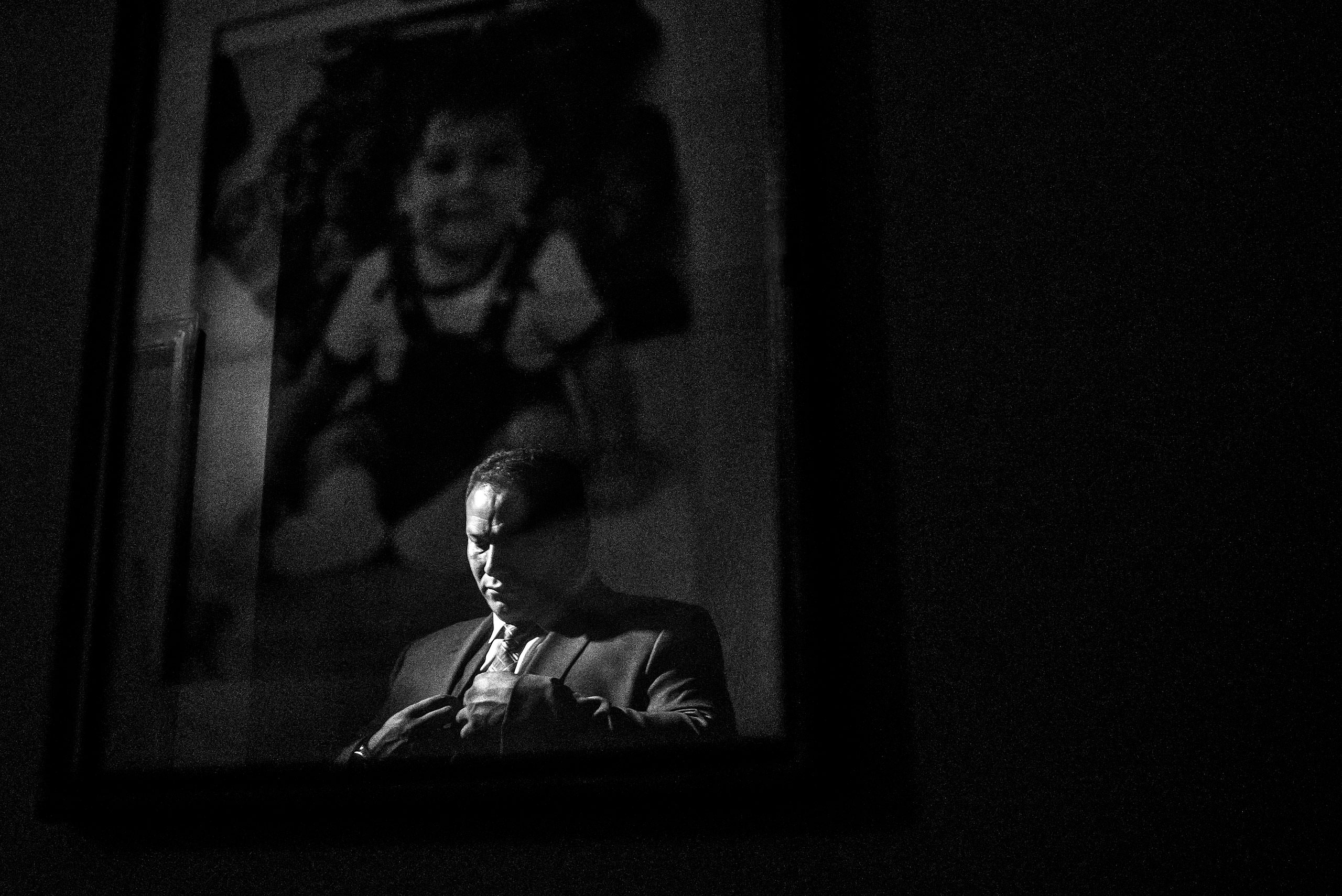 a reflection of a groom in a photo hanging on a wall by Edmonton wedding photographer sean leblanc