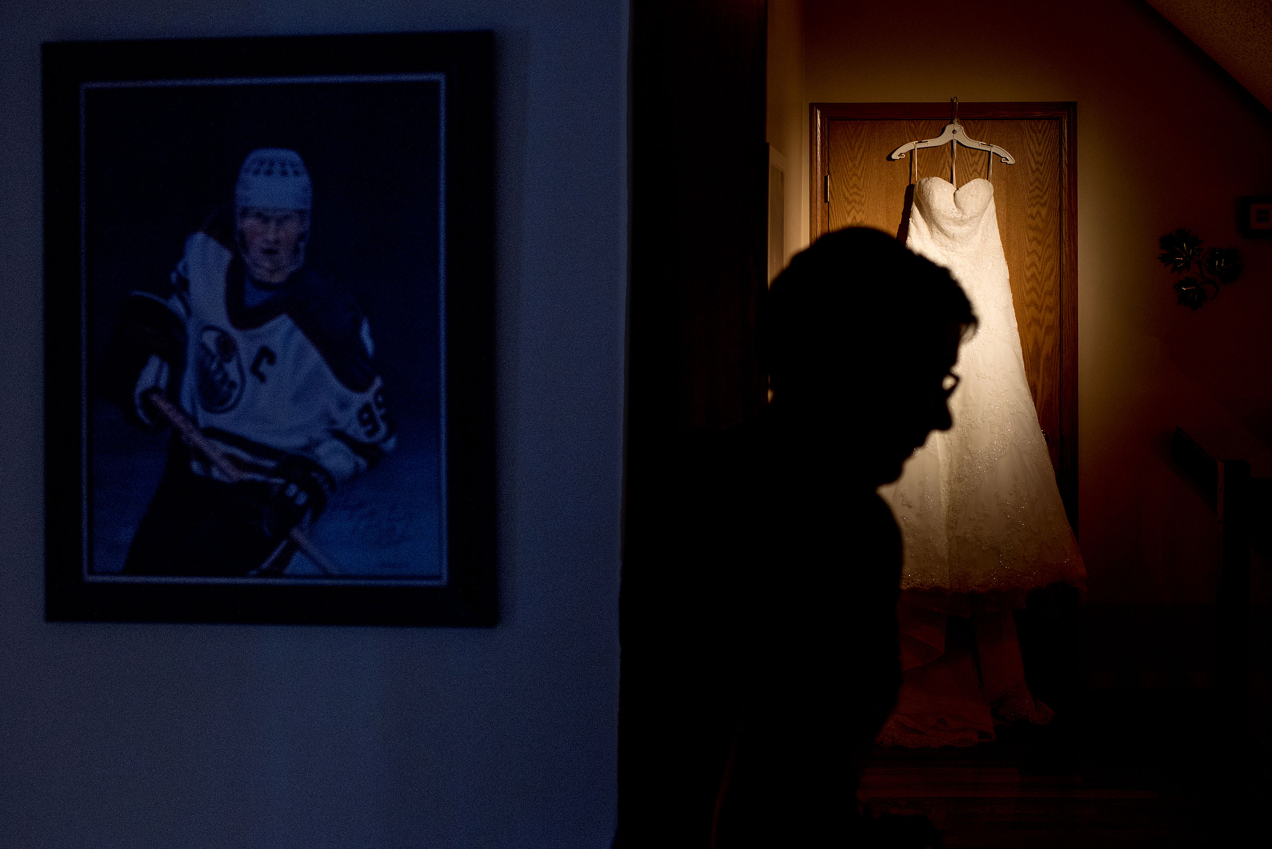a mother of a bride walks past a wedding dress with Wayne Gretzky photograph hanging on the wall by Edmonton wedding photographer sean leblanc